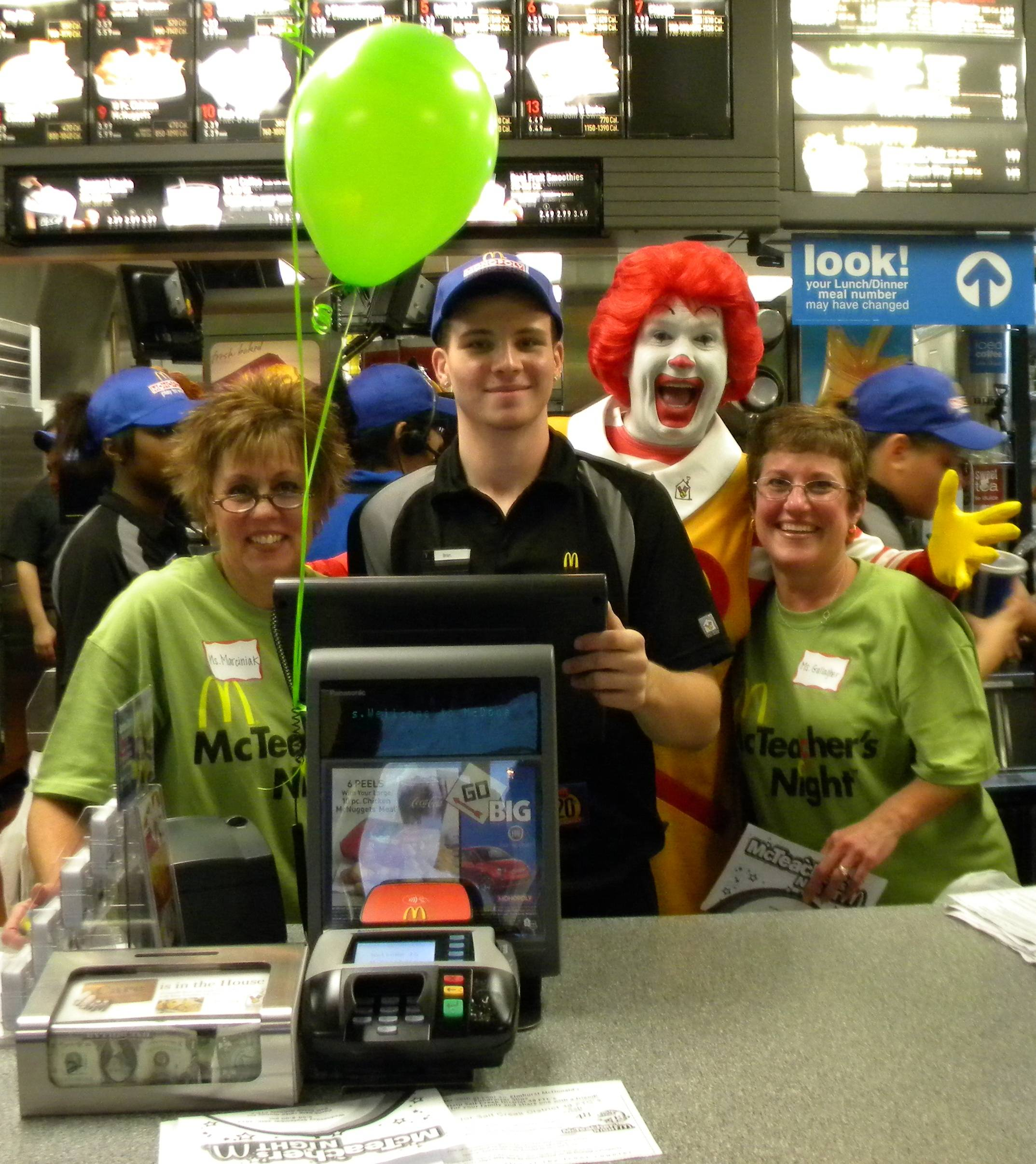 Ms. Marciniak and Ms. Gallagher all smiles with Ronald McDonald behind the counter.