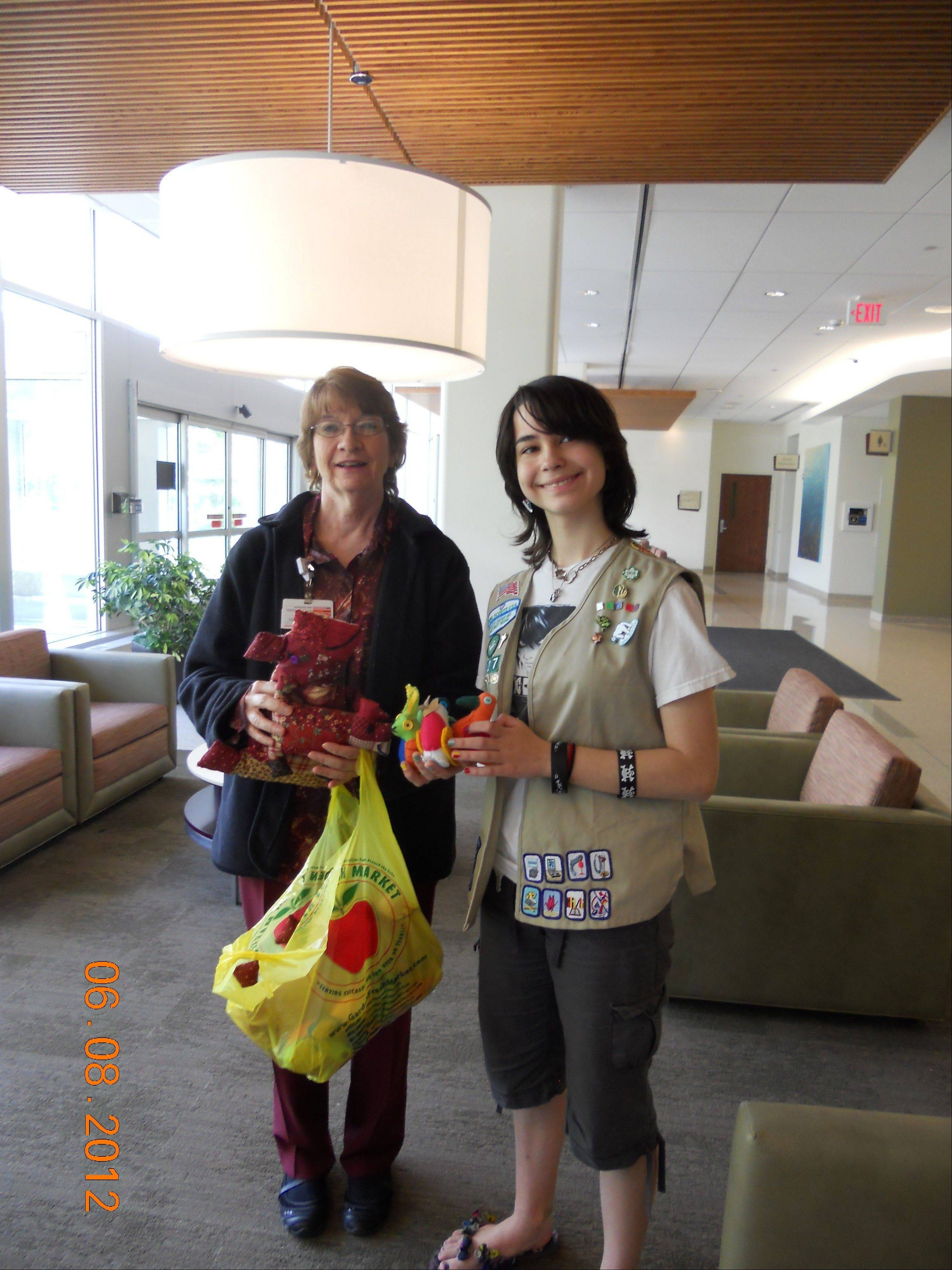 Cadette Girl Scout Maggie Scanlan delivers the stuffed animals to volunteer coordinator Gail Kreer at Northwest Community Hospital.