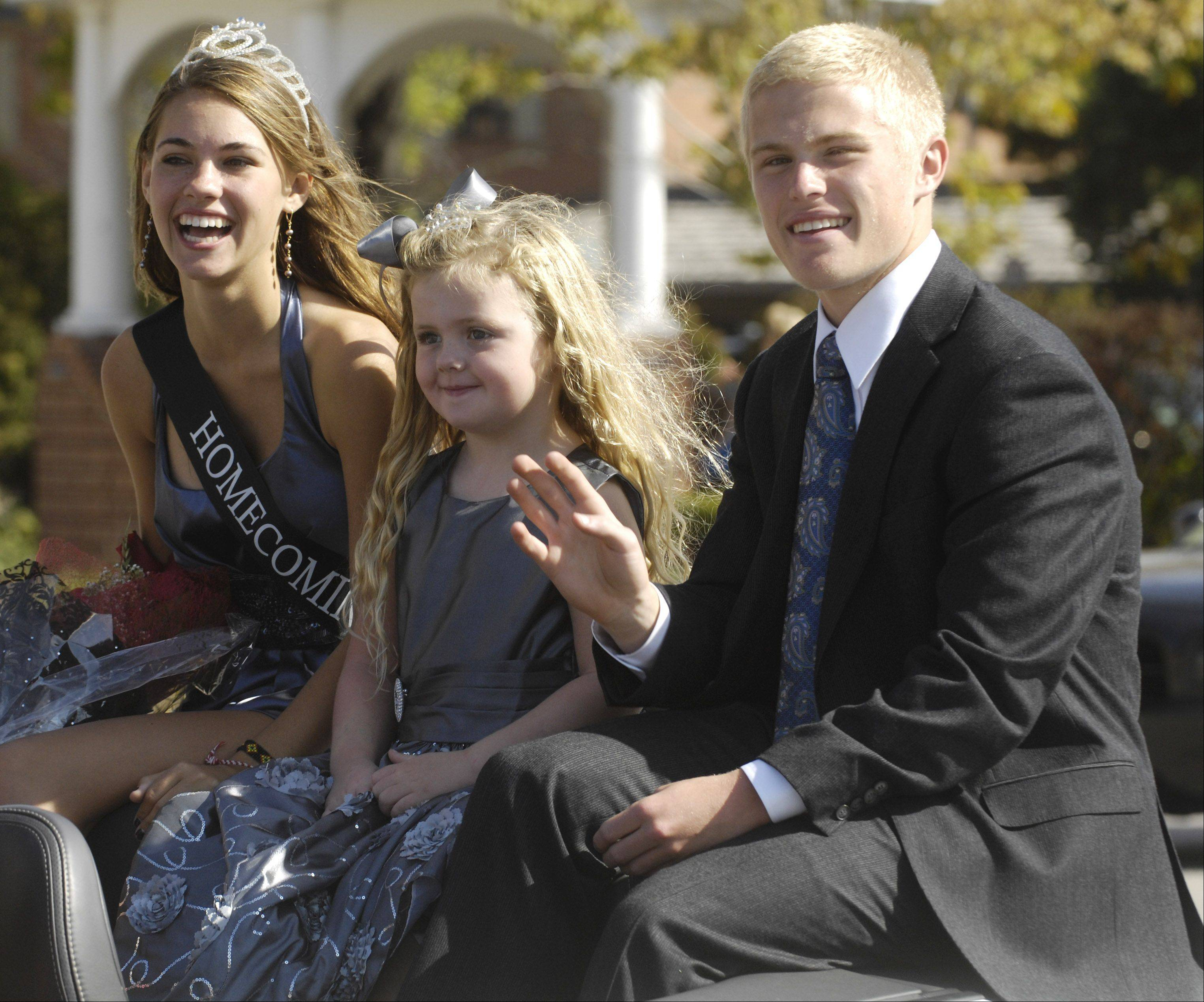 Homecoming Queen Liz Diamond rides with Elle McLaughlin, 6, and escort Zach Rowe during the Barrington High School homecoming parade Saturday.