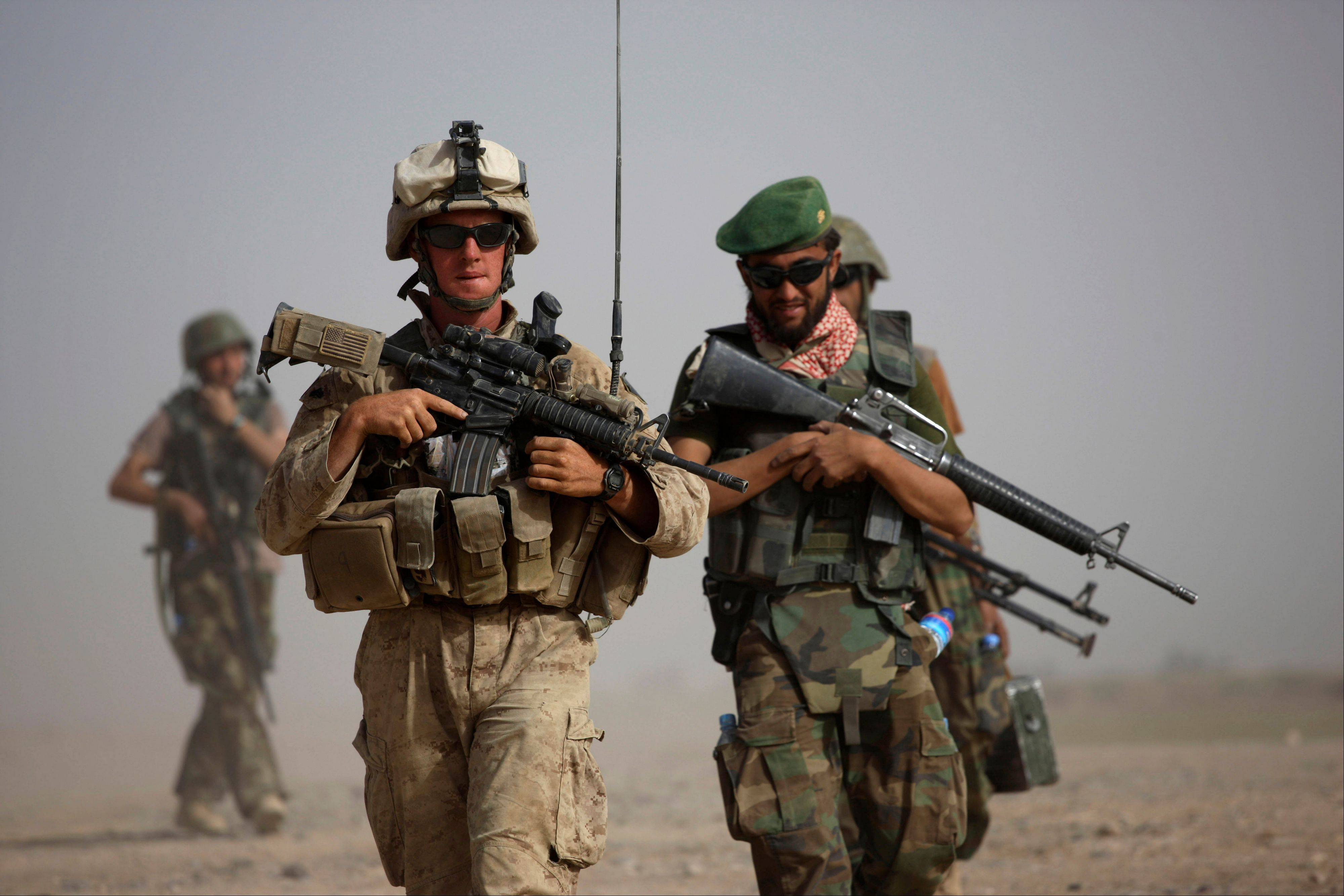 U.S. Marine squad leader Sgt. Matthew Duquette, left, of Warrenville, with Bravo Company, 1st Battalion 5th Marines walks with Afghan National Army Lt. Hussein, during in a joint patrol in Nawa district, Helmand province, southern Afghanistan. U.S. military officials have noted that Afghan security forces are dying in insider attacks along with foreign troops, but so far, the Afghan government has not provided statistics on the number killed.