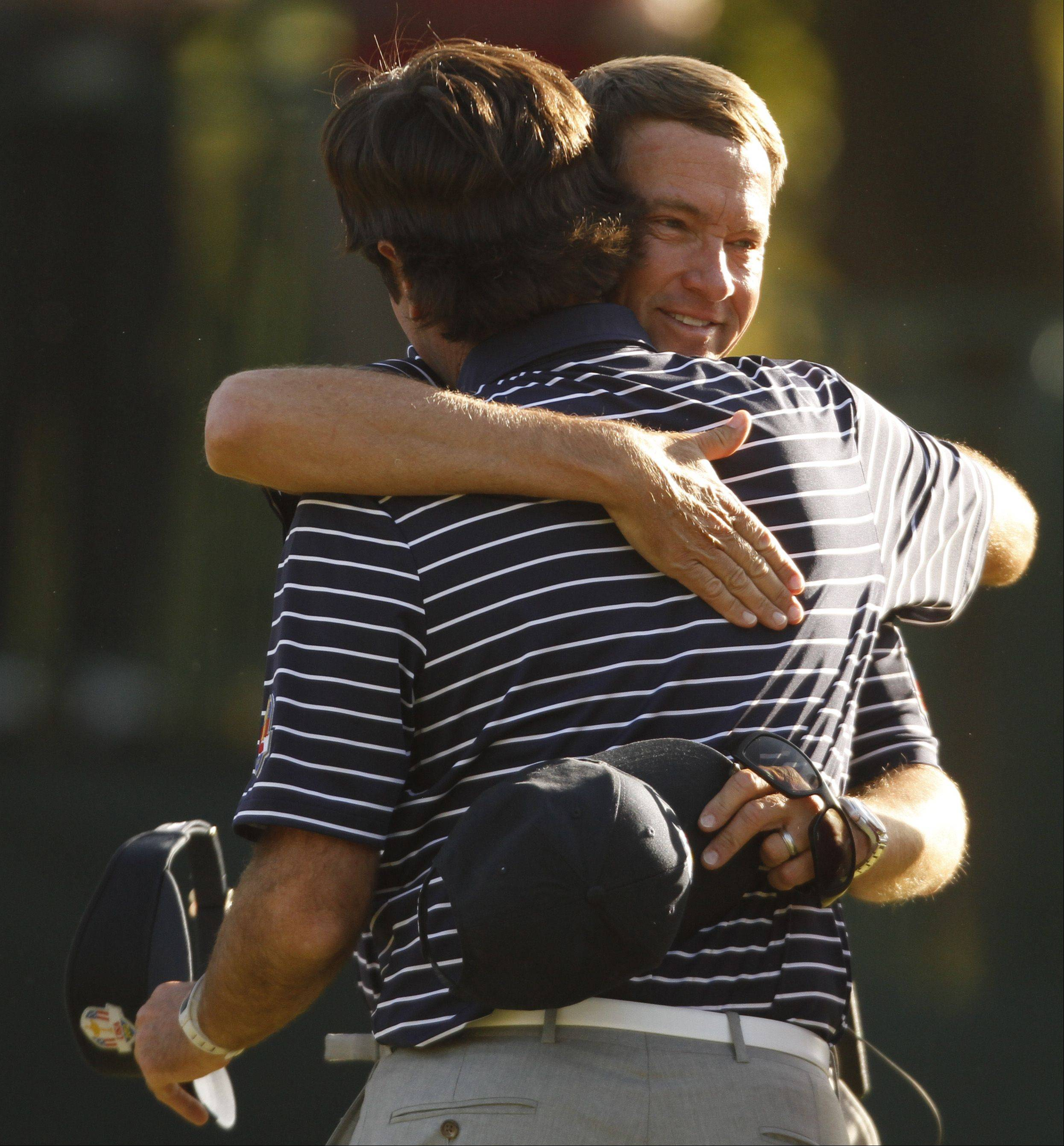 Team USA captain Davis Love III hugs Bubba Watson after Watson and teammate Webb Simpson won their match Saturday afternoon.