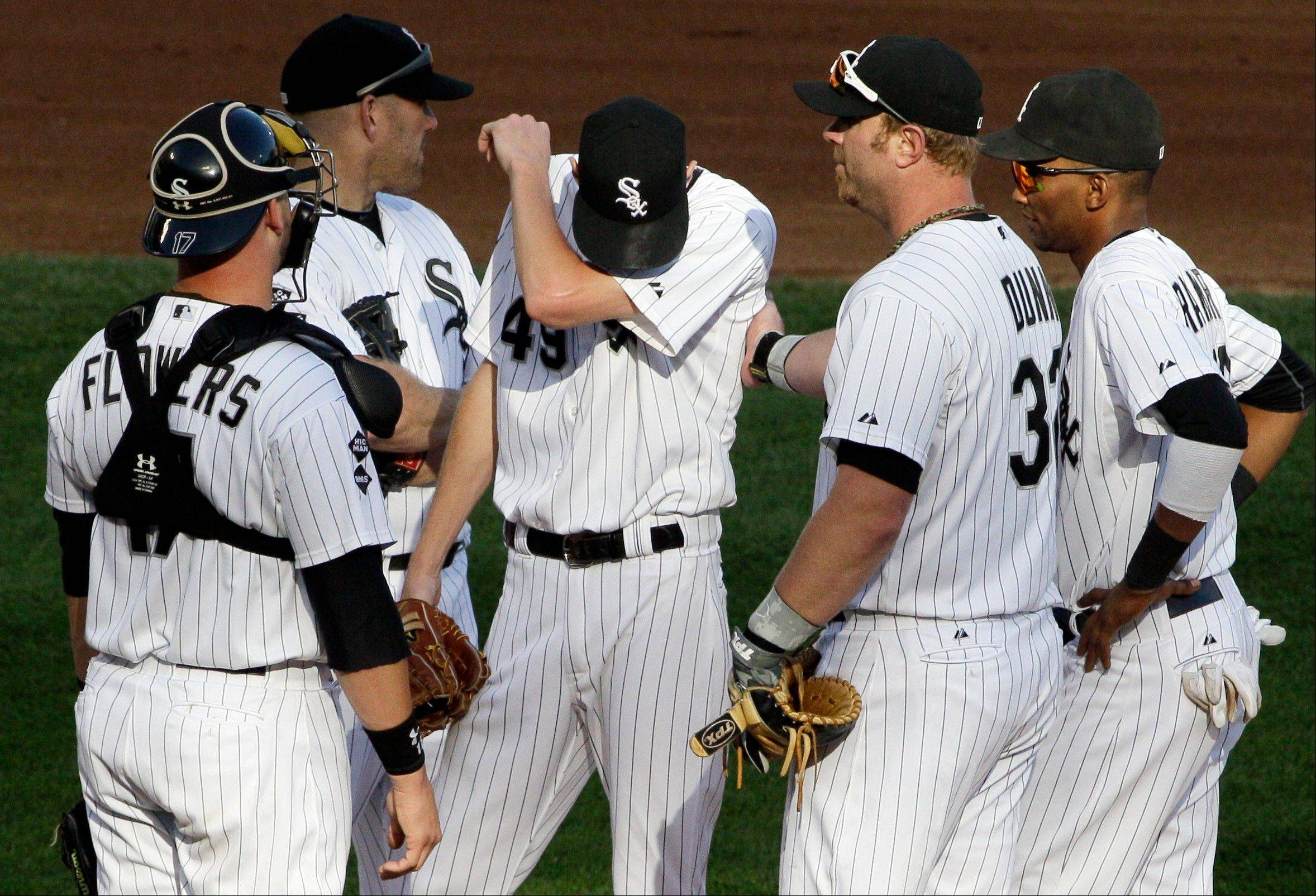 White Sox starter Chris Sale, middle, wipes his face Saturday as catcher Tyler Flowers (17), third baseman Kevin Youkilis (20), first baseman Adam Dunn (32) and shortstop Alexei Ramirez (10) react after Tampa Bay Rays' B.J. Upton hit a one-run single during the fourth inning.