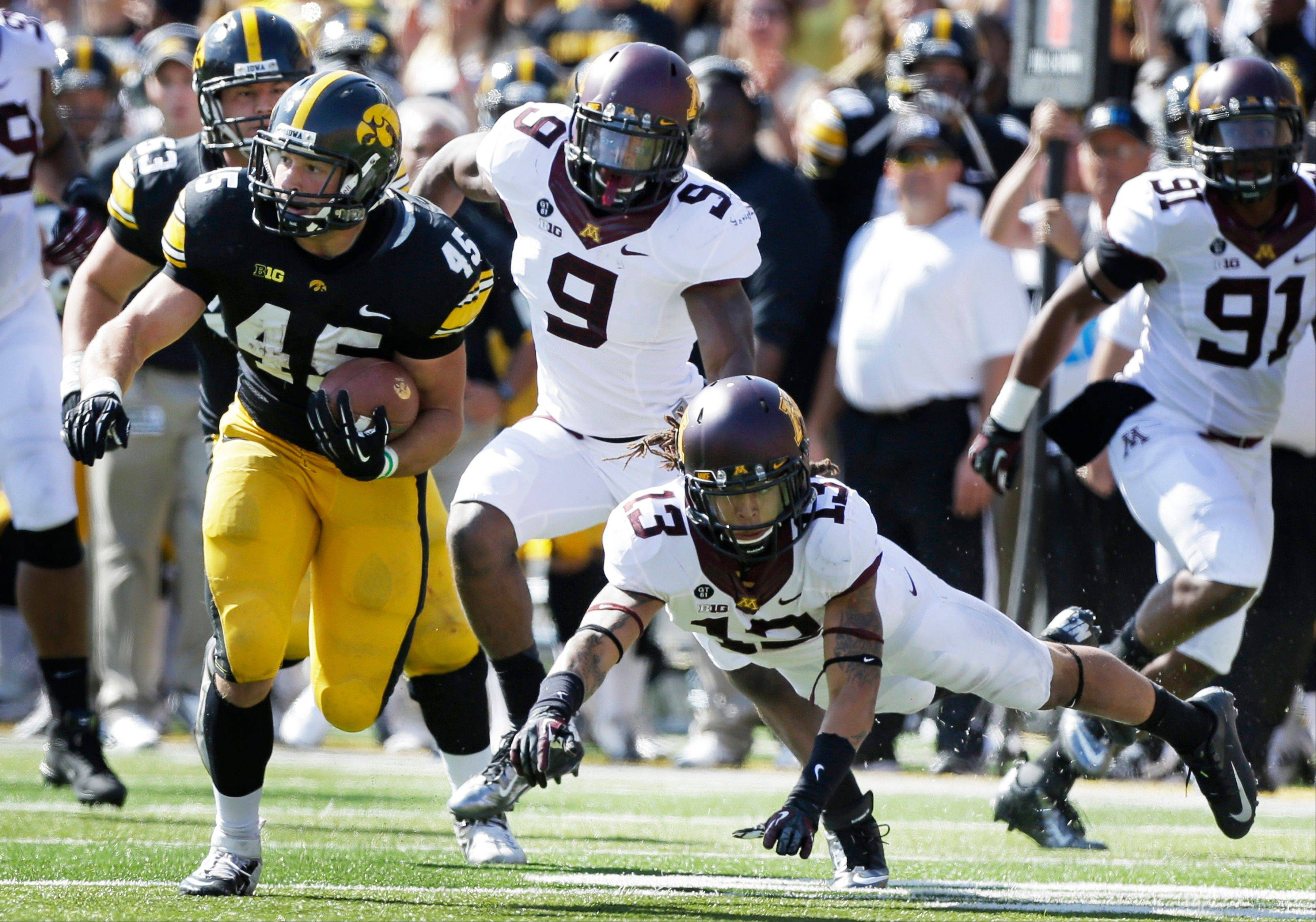 Iowa fullback Mark Weisman runs from Minnesota defenders James Manuel (9) and Derrick Wells (13) Saturday during the first half in Iowa City, Iowa.