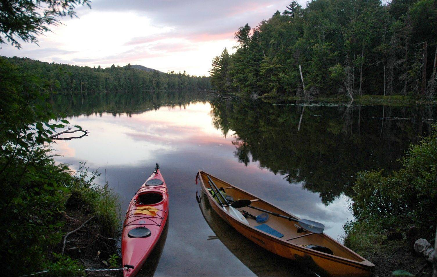 A kayak and solo canoe rest at a campsite on East Pine Pond in the Saranac Lakes Wild Forest at Saranac Lake, N.Y.