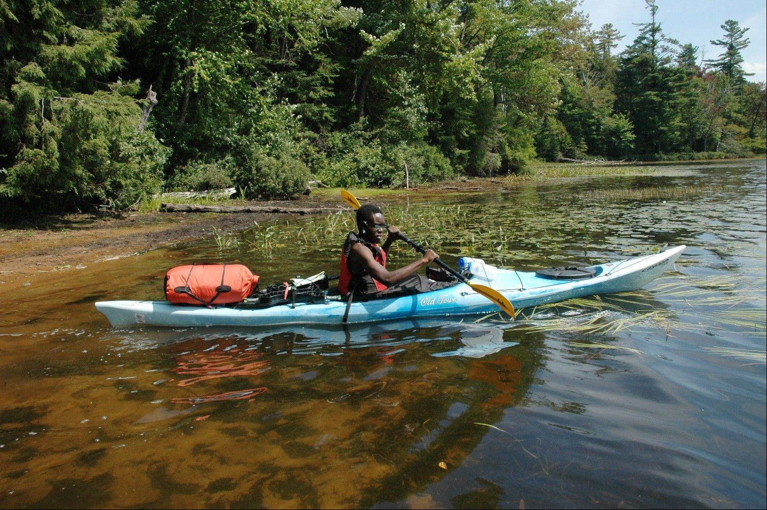 "Tolu Fashoro, of Troy, N.Y., paddles a kayak loaded with camping gear onto Floodwood Pond in the Saranac Lakes Wild Forest in Saranac Lake, N.Y. A new guidebook, ""Adirondack Paddling: 60 Great Flatwater Adventures,"" is due out this year, aimed at the growing number of people exploring the expanding opportunities for paddlers in the Adirondack Park."