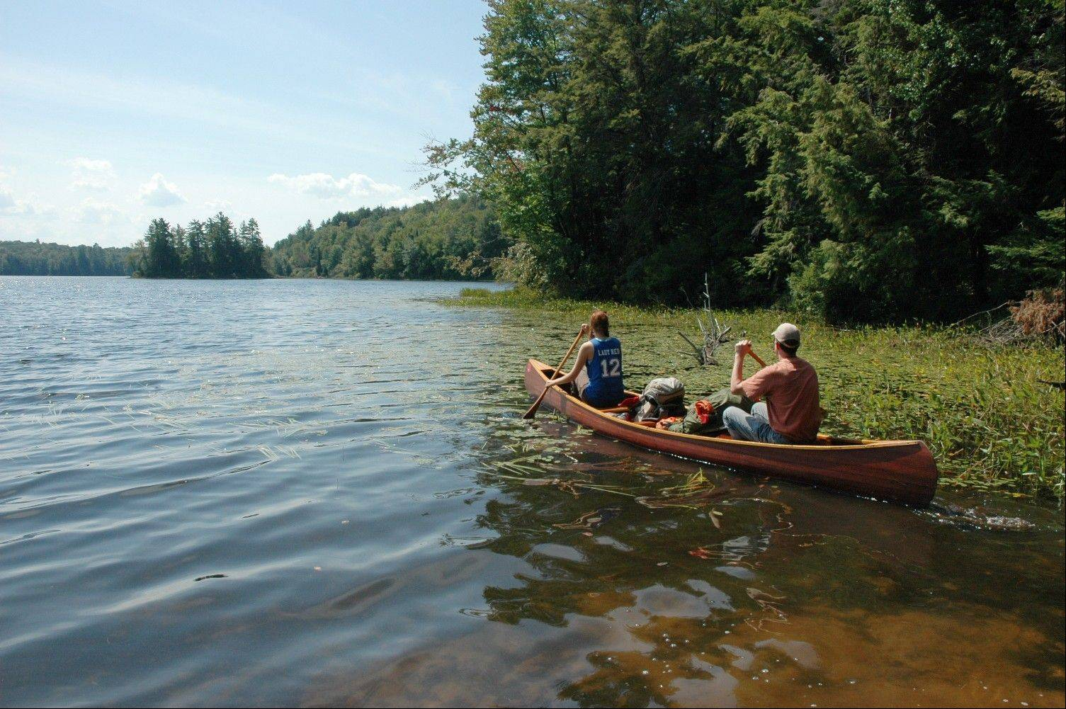 Leah and Bruce Nelson, of Albany, N.Y., paddle a canoe loaded with camping gear onto Floodwood Pond in the Saranac Lakes Wild Forest at Saranac Lake, N.Y.