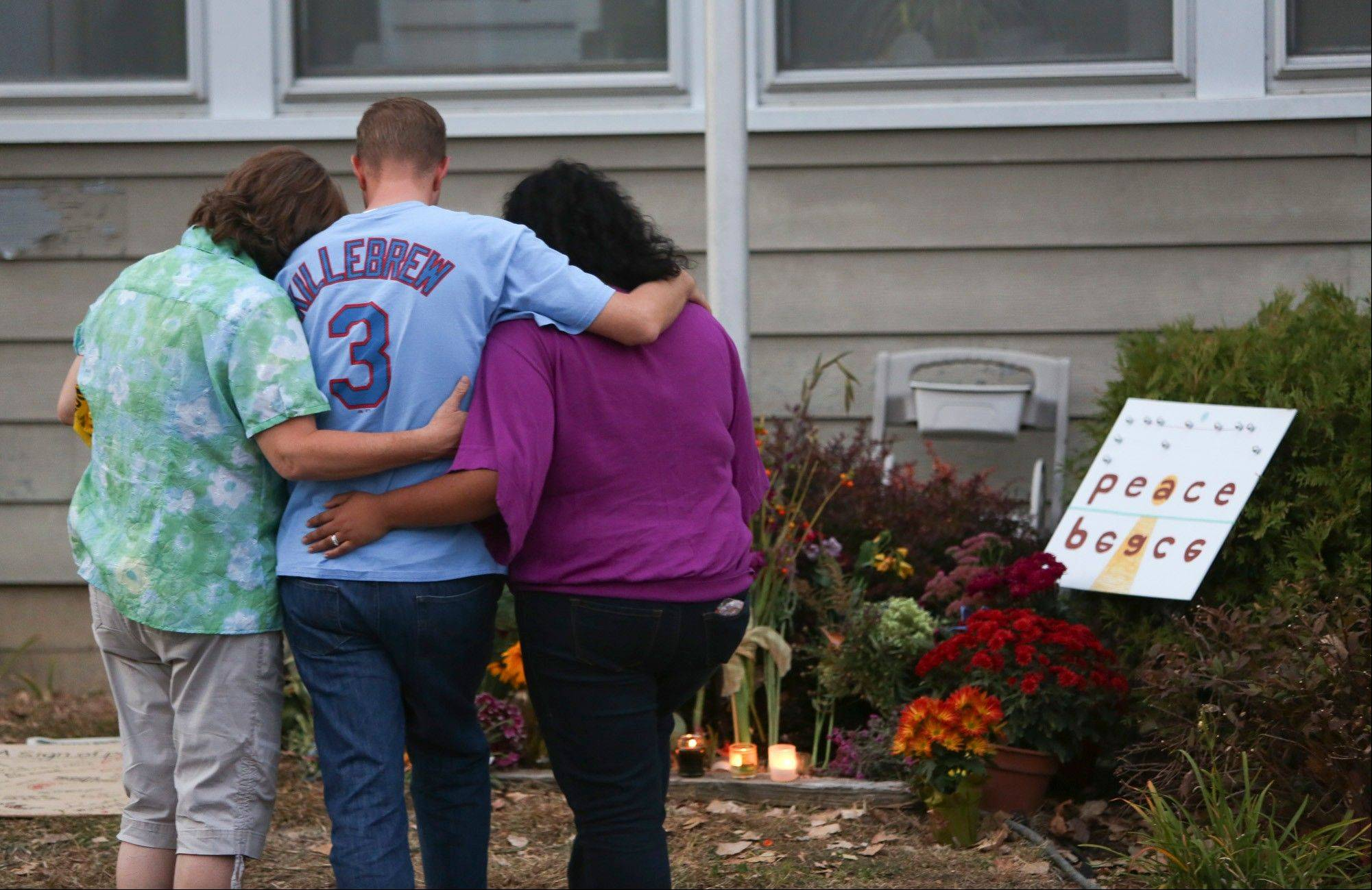 A family members of Ron Edberg consoled his son, Dusty, center, Saturday in front of an informal memorial made for the victims in front of Accent Signage Systems in Minneapolis, Minn.