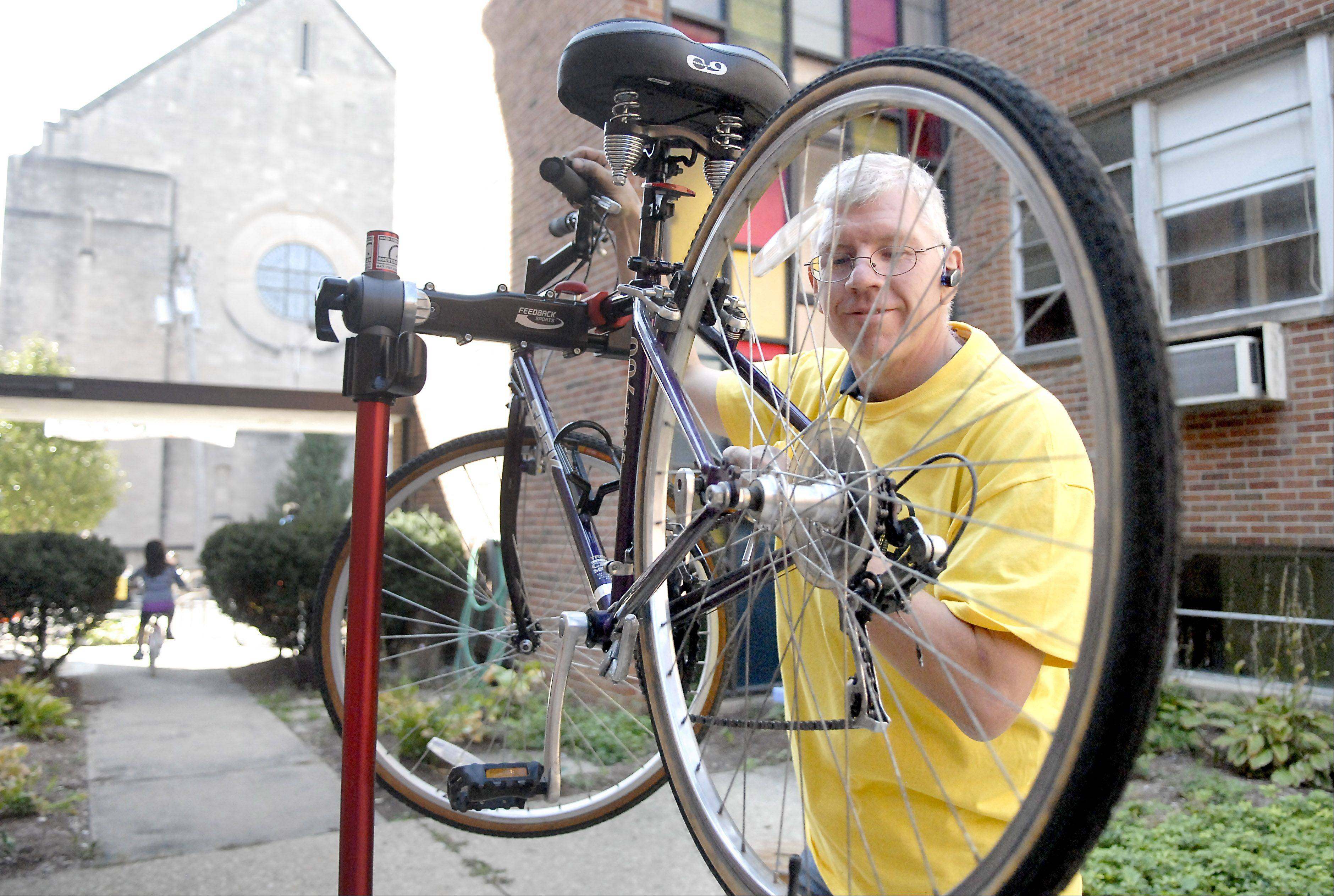 Volunteer Jeff Bratko of East Dundee gets a bike chain running smoothly in the courtyard of Vineyard Church at the Love Elgin Day event on Saturday, September 29. This was the second year bike enthusiast Bratko, who is a member of the Vineyard Church of Elgin, has helped at the event.