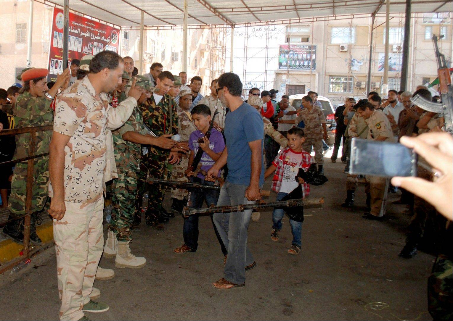 Libyan civilians turn in weapons to security forces Saturday in Benghazi, Libya. Hundreds of Libyans have converged on a main square in Benghazi in response to a call from the military to hand over their weapons, some driving in with armored personnel carriers, vehicles with mounted anti-aircraft guns and hundreds of rocket launchers.