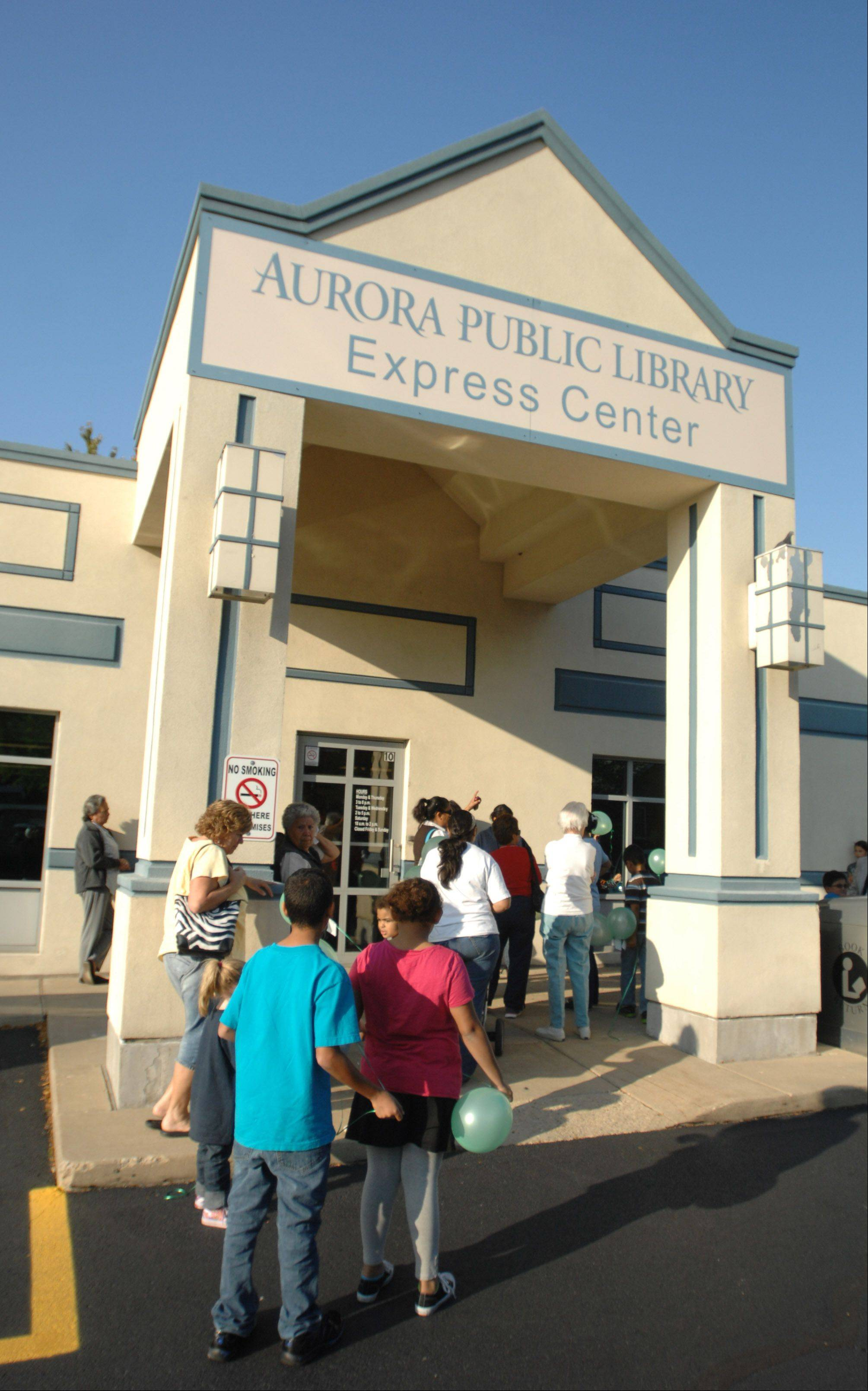Local children wait for the doors to open at the new Aurora Public Library's Express Center Friday. It's been open since Sept. 17, but Friday was a special event to welcome the public.