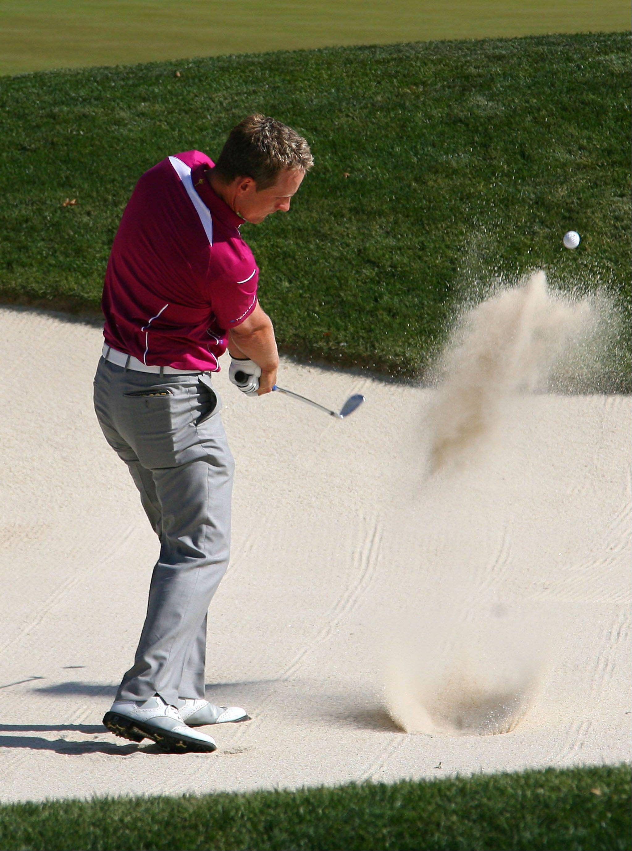 Luke Donald hits out of the trap on the 6th hole during Ryder Cup fourball matches Saturday at Medinah Country Club. He captured his first point of this Ryder Cup when he and Sergio Garcia defeated Tiger Woods and Steve Stricker on the 18th hole.