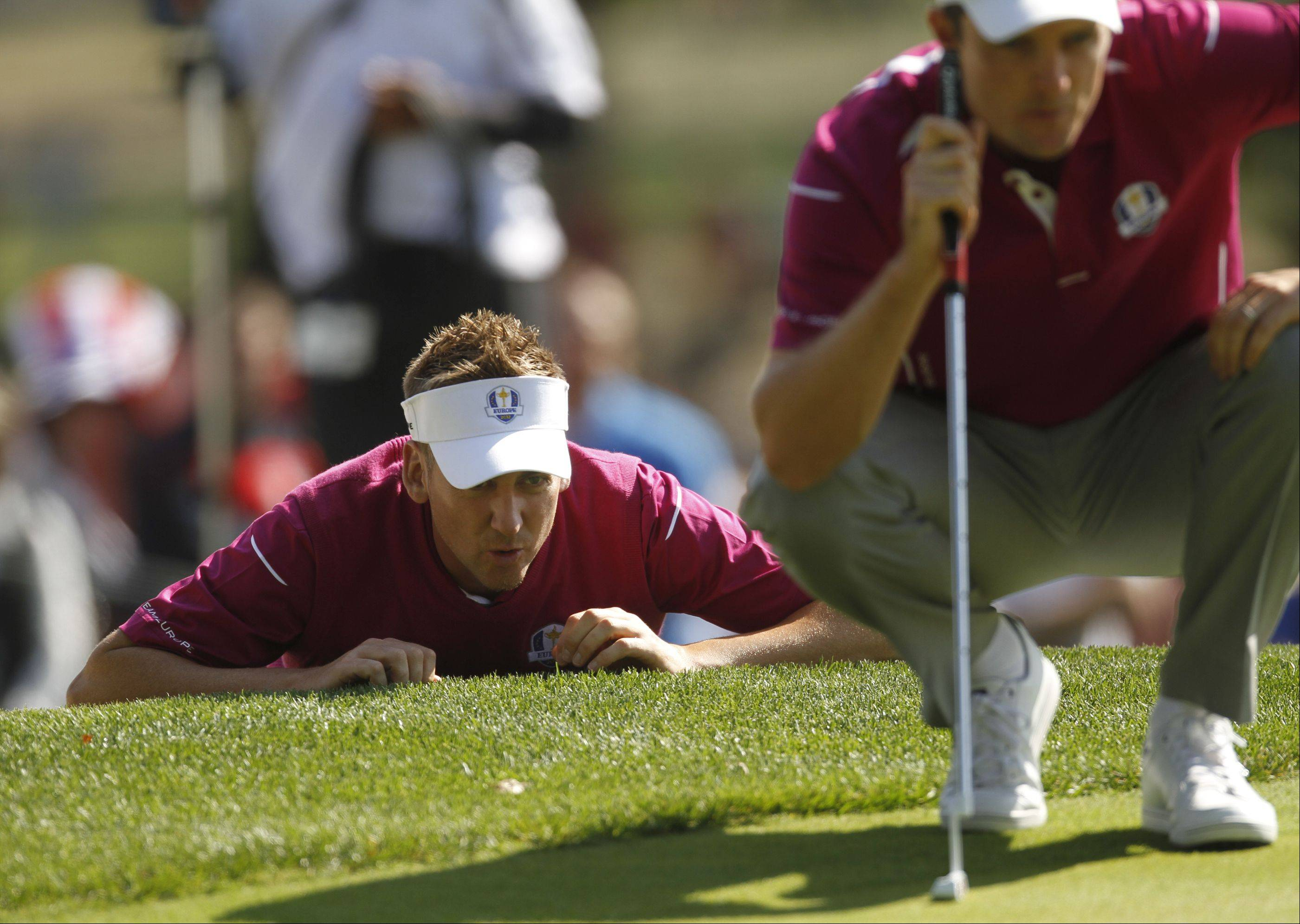 Ian Poulter, left, helps, helps Justin Rose line up his putt on the 16th hole Saturday morning during Day 2 of the Ryder Cup at Medinah Country Club.