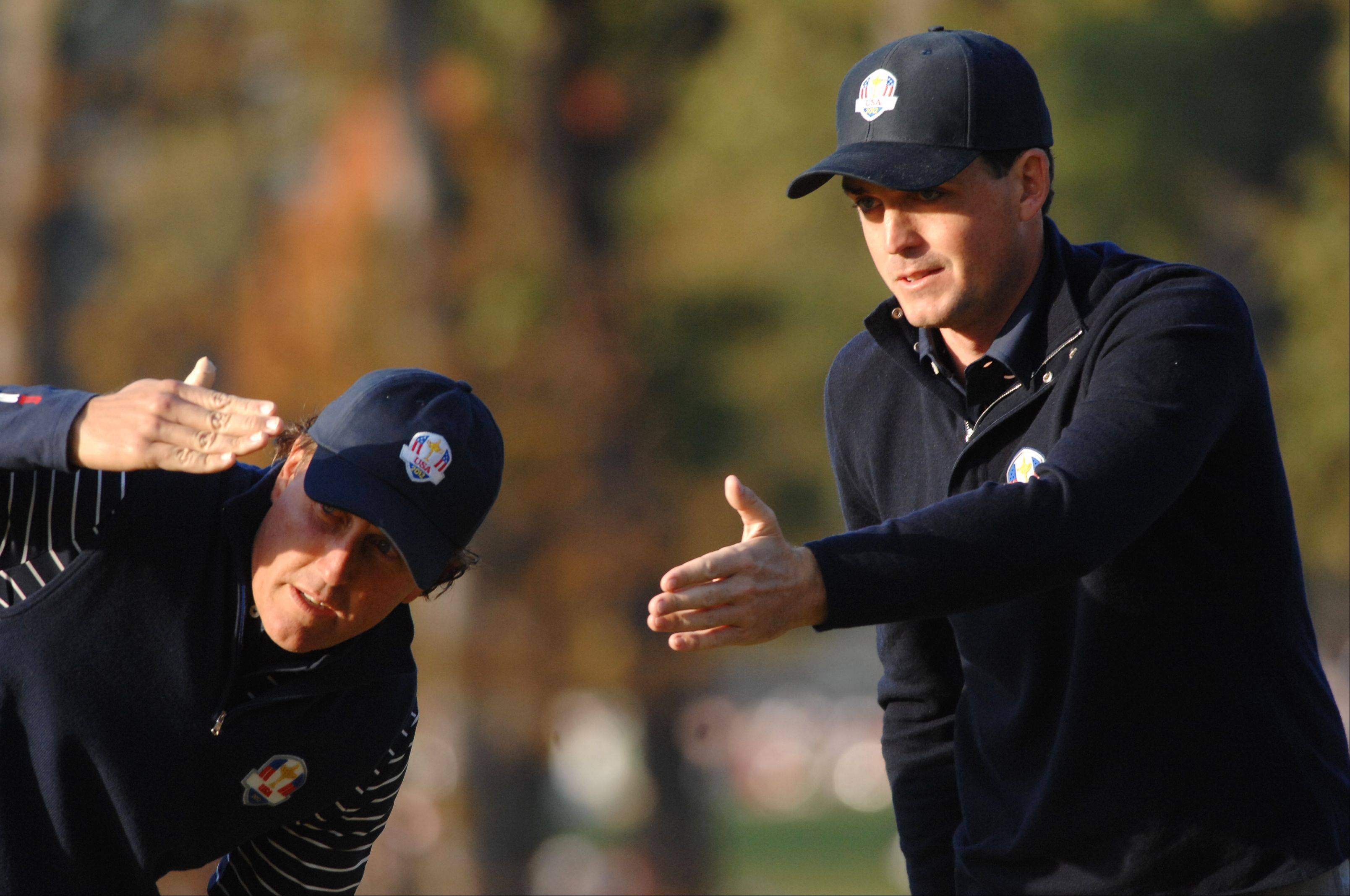Keegan Bradley, right, and playing partner Phil Mickelson work on lining up a putt on the 4th hole Saturday morning during day 2 of the 2012 Ryder Cup at Medinah Country Club.