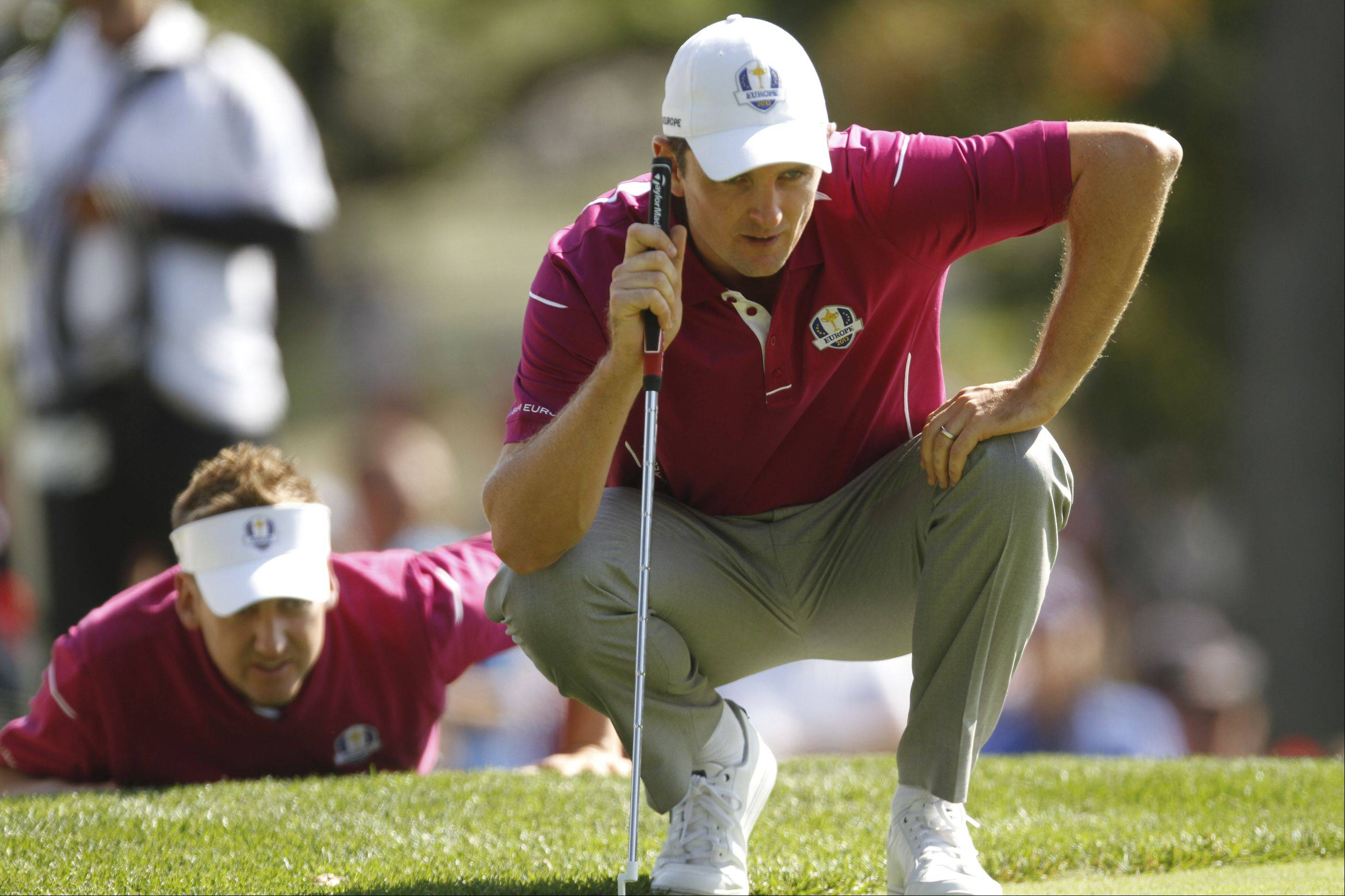 Ian Poulter, left, helps, helps Justin Rose line up his putt on the 16th hole Saturday morning during day 2of the 2012 Ryder Cup at Medinah Country Club.