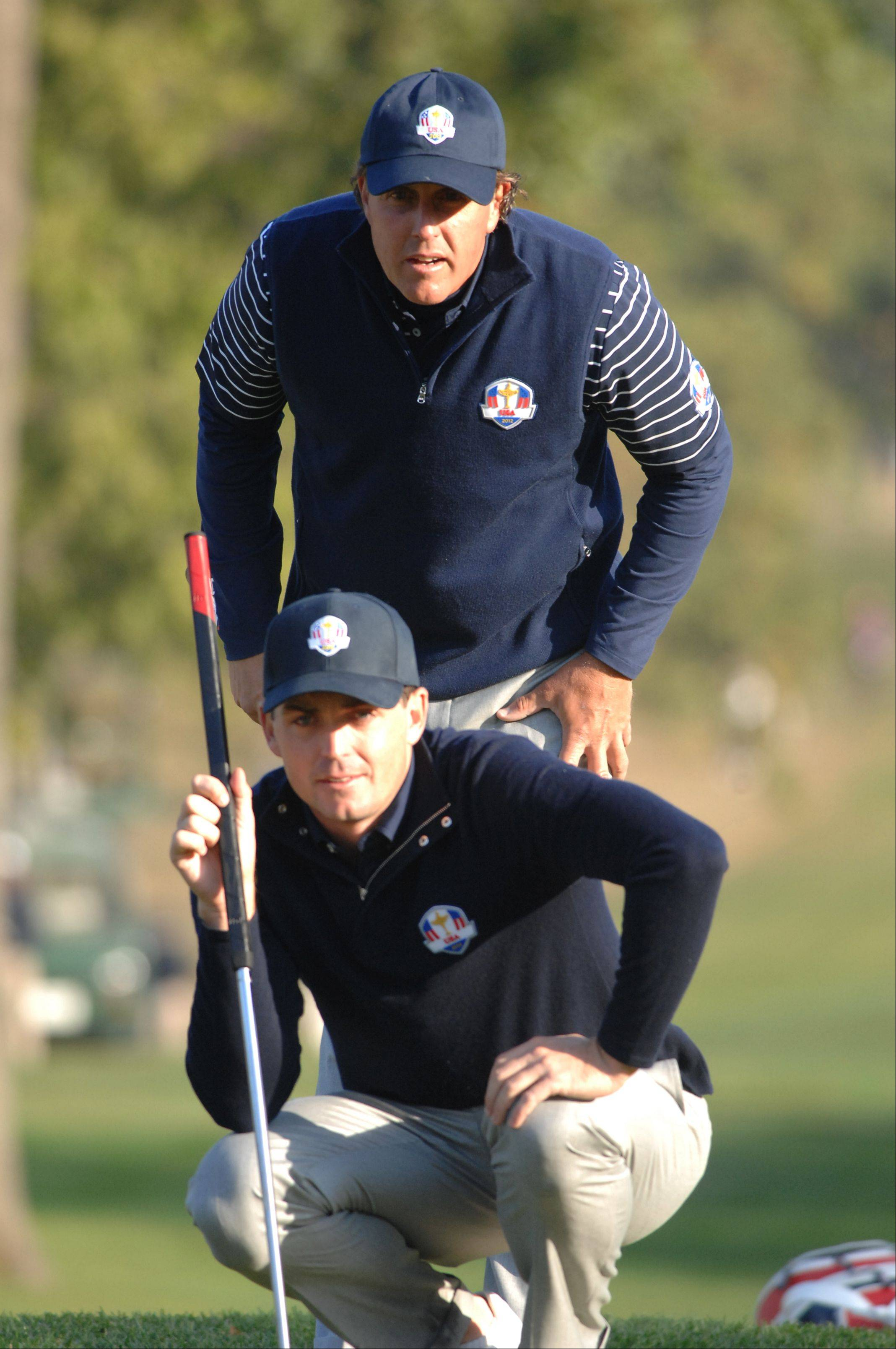 Phil Mickelson, standing, and Keegan Bradley line up Mickelson's putt on the 4th hole Saturday morning during day 2 of the 2012 Ryder Cup at Medinah Country Club.