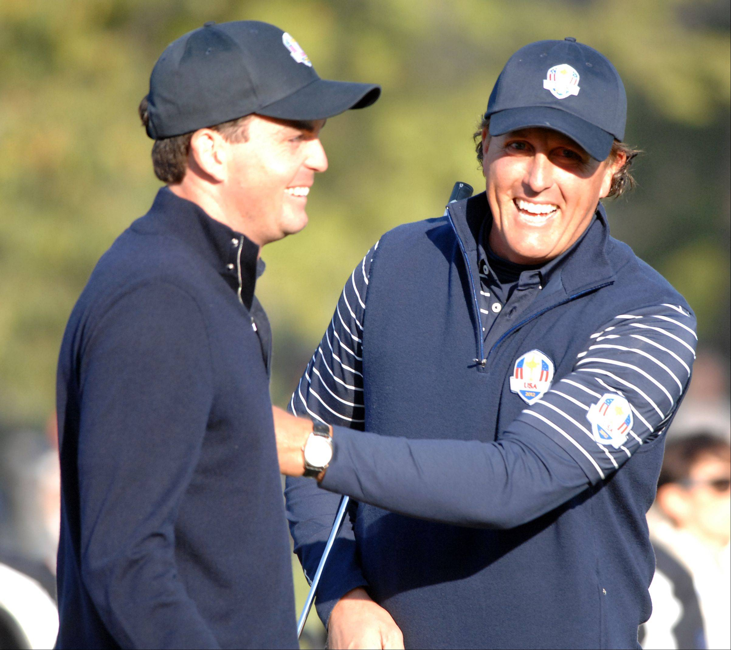 Phil Mickelson and Keegan Bradley celebrate after winning the 4th hole Saturday morning during day 2 of the 2012 Ryder Cup at Medinah Country Club.