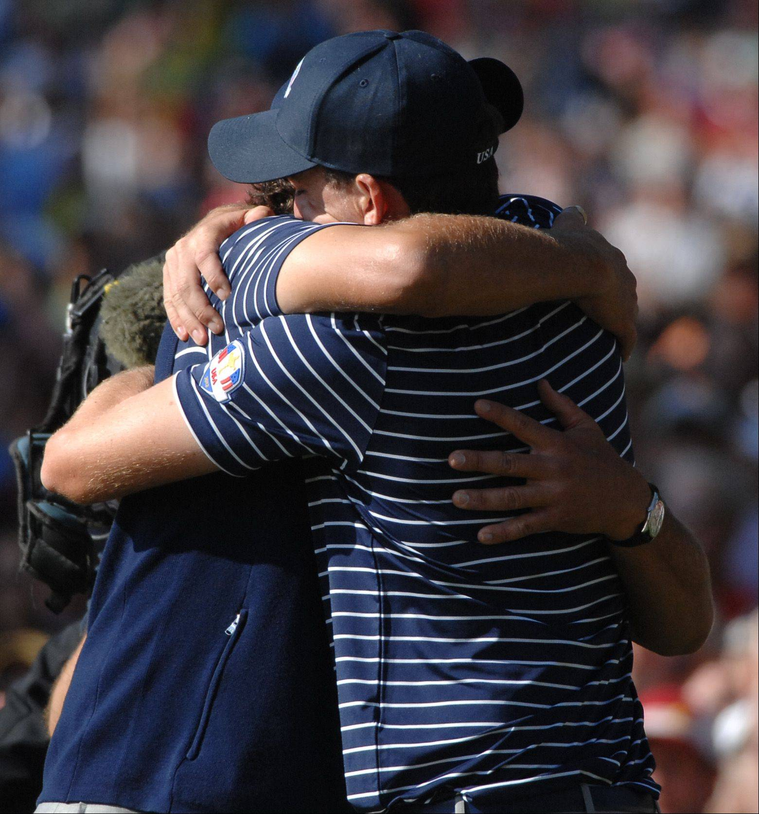 Teammates Phil Mickelson and Keegan Bradley hug after beating team Europe on the 12th hole Saturday during the foursome matches.