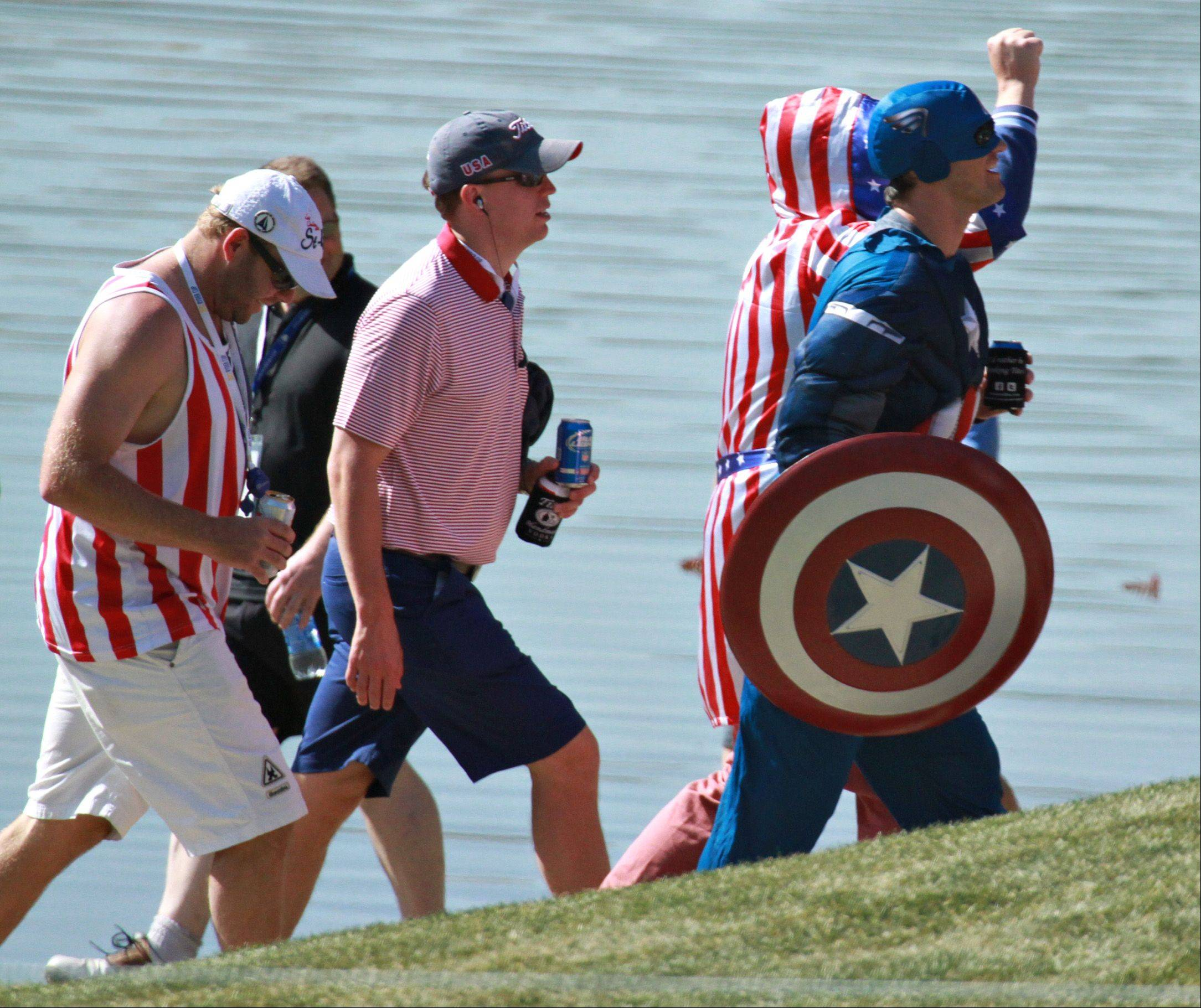 Captain America and some other red, white and blue fans make their way from hole to hole watching the golf action Saturday.