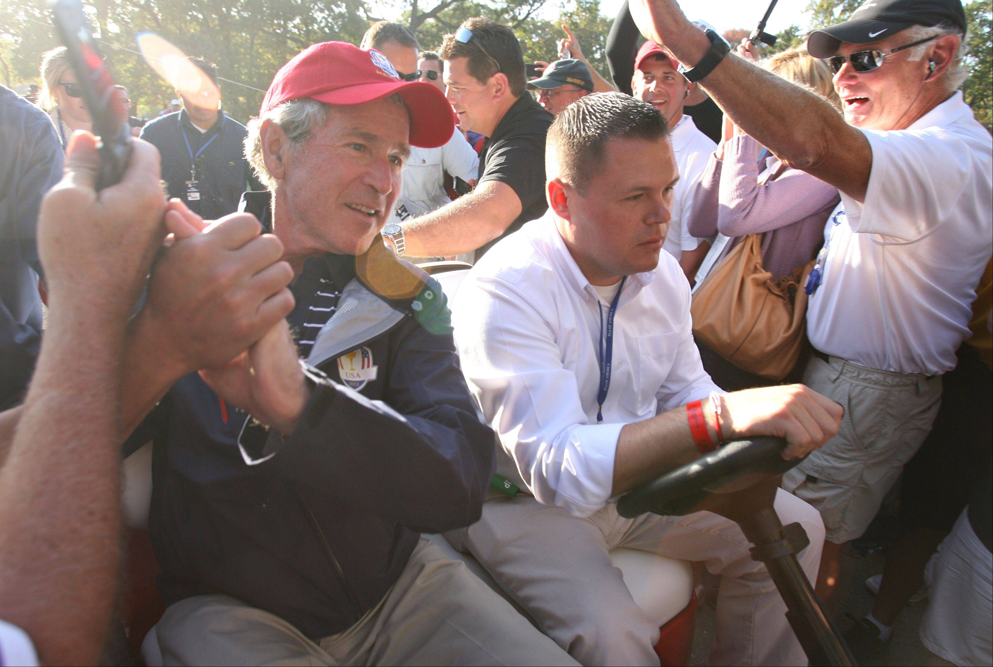President George W. Bush is escorted by golf cart through a crowd of golf fans Saturday afternoon in Medinah.
