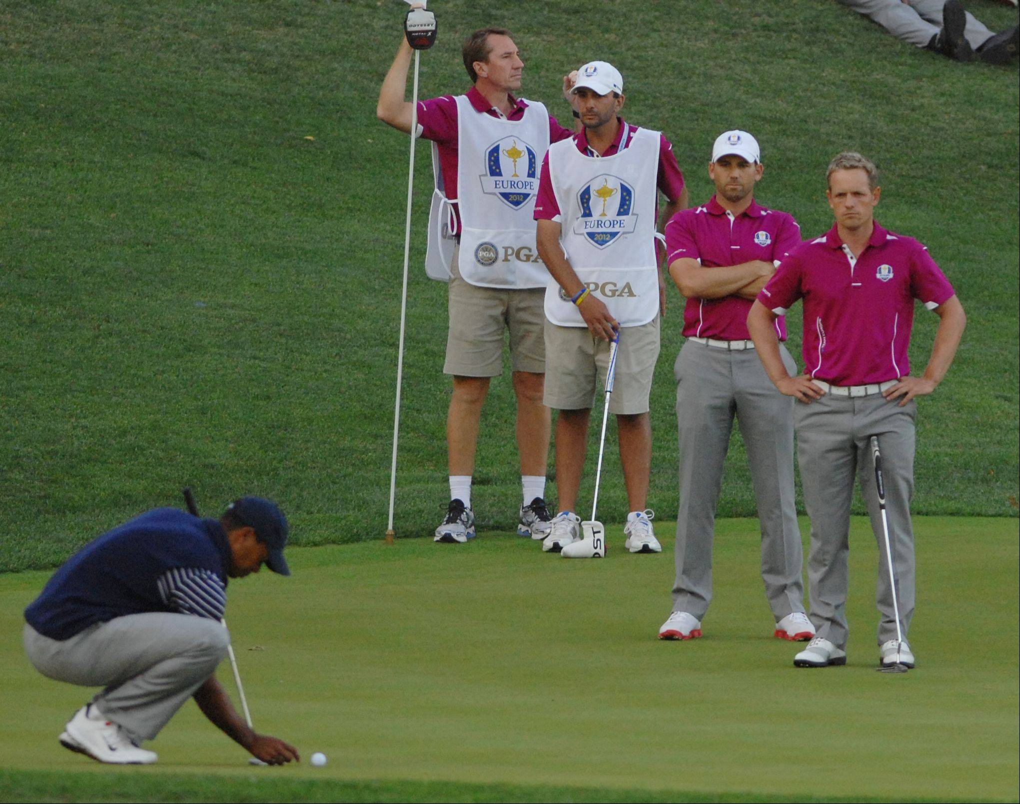 Team Eurorpe's Luke Donald, right, and Sergio Garcia keep a close eye on Tiger Woods as he lines up his birdie putt on 17 Saturday afternoon on day 2 of the 2012 Ryder Cup at Medinah Country Club.