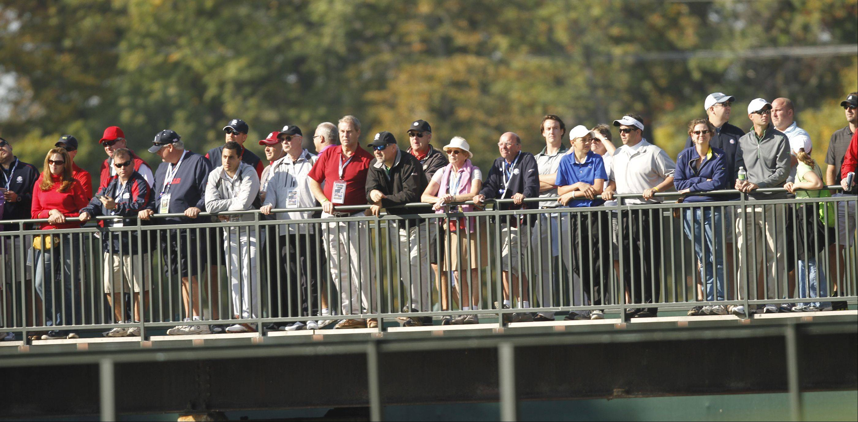 Fans watch the action on from the bridge on the 13th hole Saturday morning during day 2 of the 2012 Ryder Cup at Medinah Country Club.