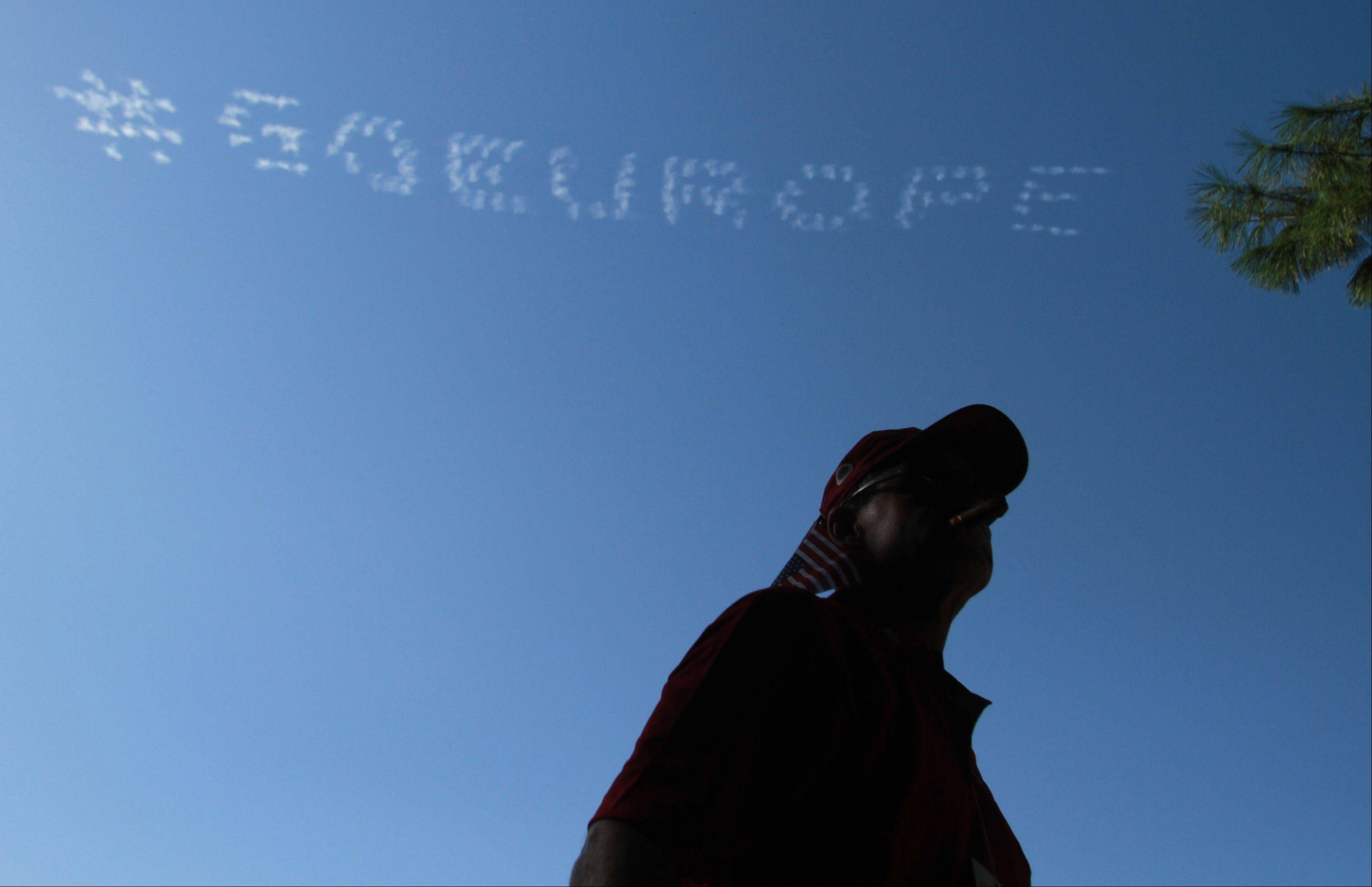 Skywriting planes painted the skies over Medinah with messages for the European team Saturday afternoon as a fan takes in the golf action.