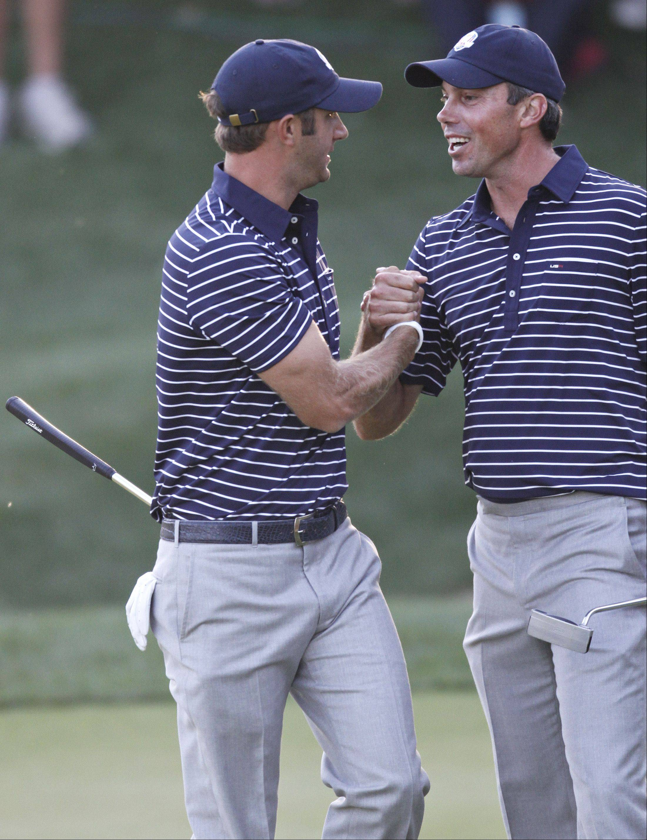 Teammates Dustin Johnson and Matt Kuchar celebrate on 17 Saturday.