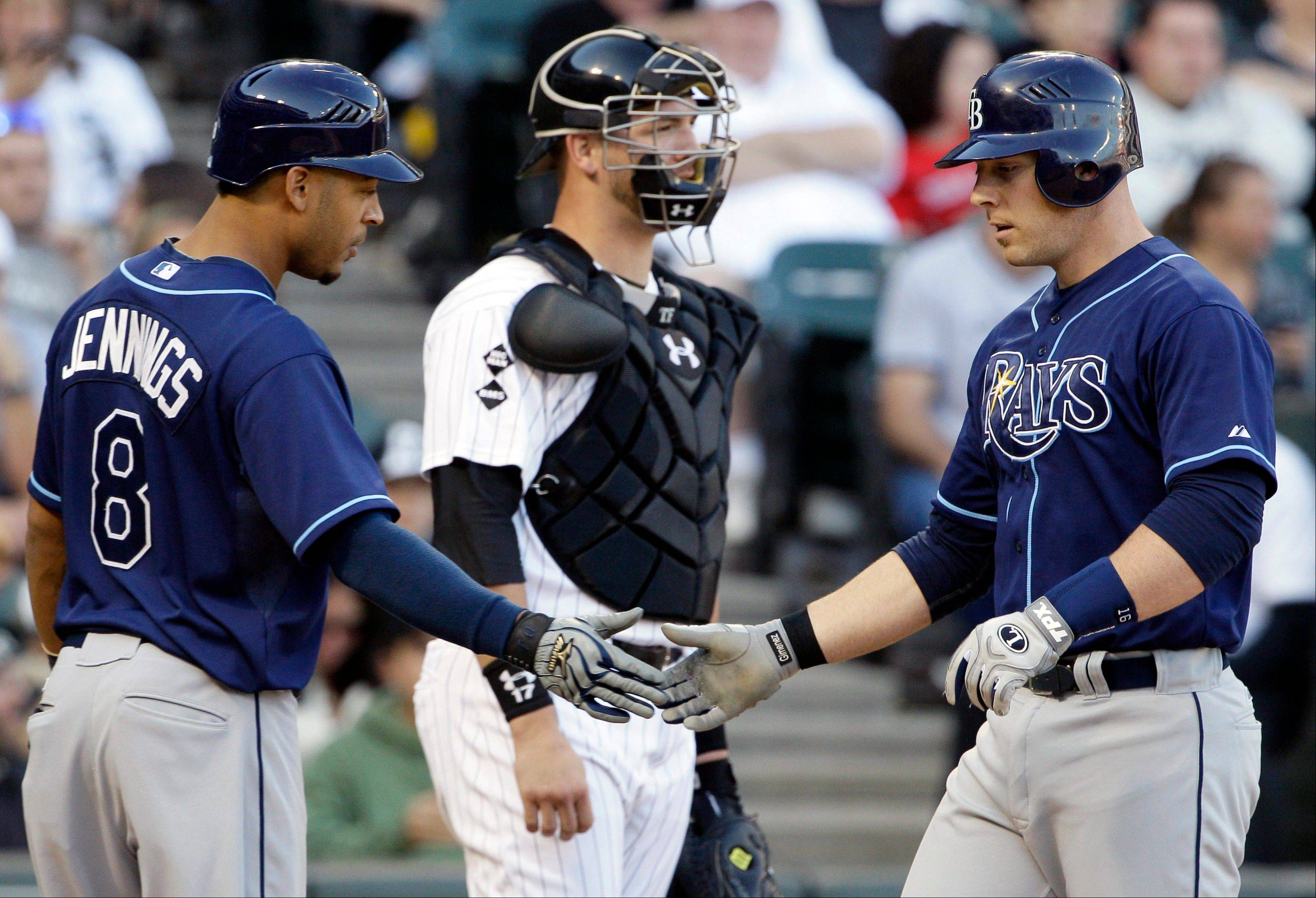 Tampa Bay Rays' Chris Gimenez, right, celebrates with Desmond Jennings, left, after hitting a solo homer. Matt Moore pitched one-hit ball into the sixth, Matt Joyce homered twice and the Tampa Bay Rays stayed three games behind in the chase for the second AL wild card Saturday by beating the sliding White Sox 10-4.