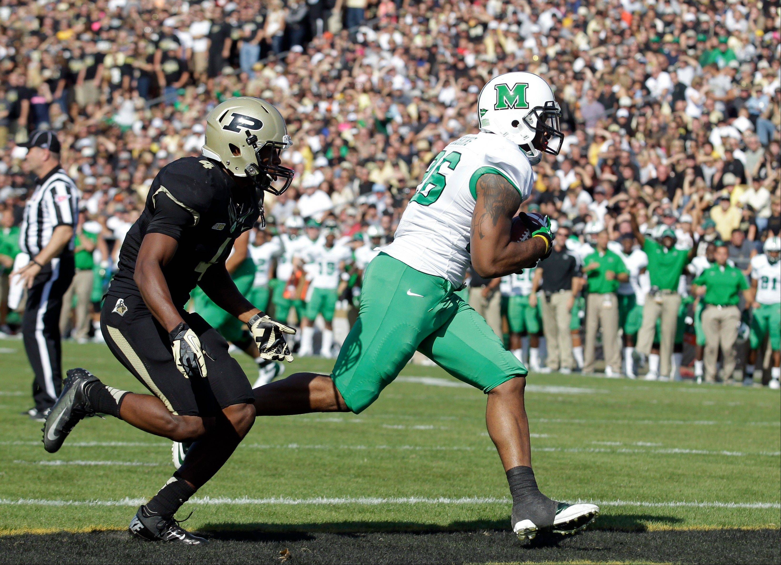 Marshall tight end Gator Hoskins, right, scores a touchdown on a 12-yard pass in front of Purdue defensive back Taylor Richards Saturday during the first half in West Lafayette, Ind.