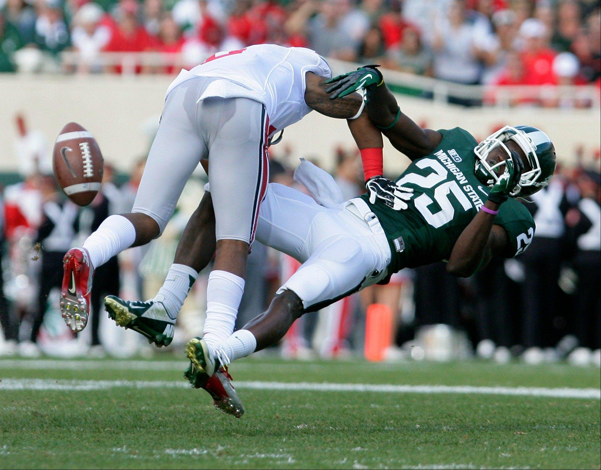 Michigan State's Keith Mumphrey is knocked off his feet by Ohio State's Rod Smith after missing a pass Saturday during the second quarter.