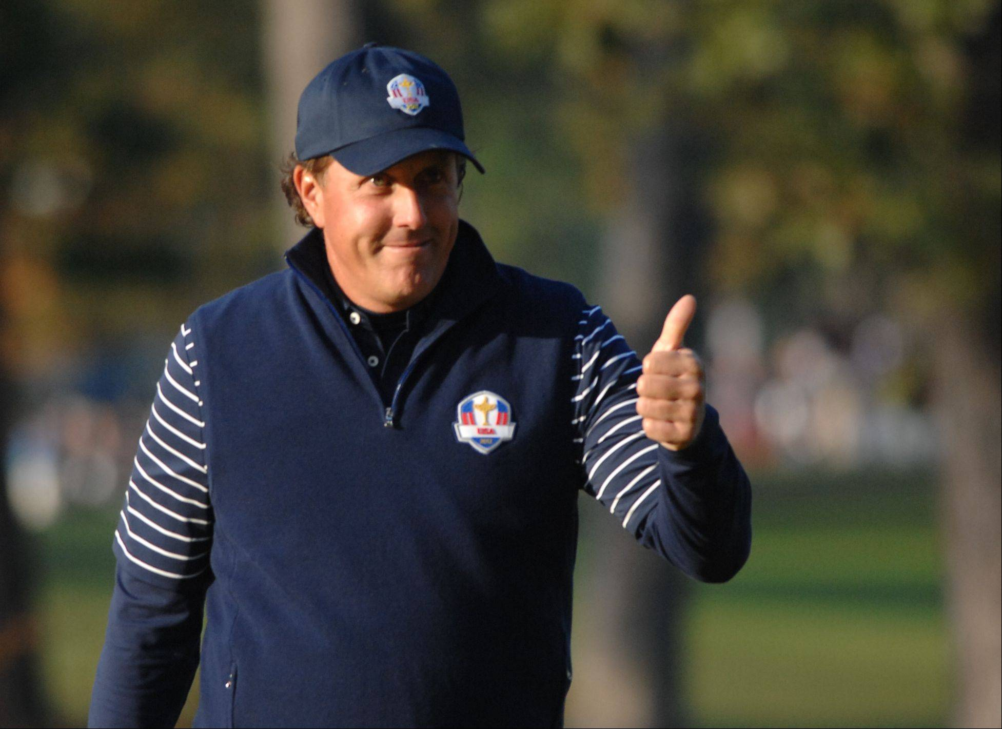 Phil Mickelson gives partner Keegan Bradley the thumbs-up for hitting a great shot from the rough on the 4th hole that landed on the green Saturday morning during Day 2 of the 2012 Ryder Cup at Medinah Country Club.