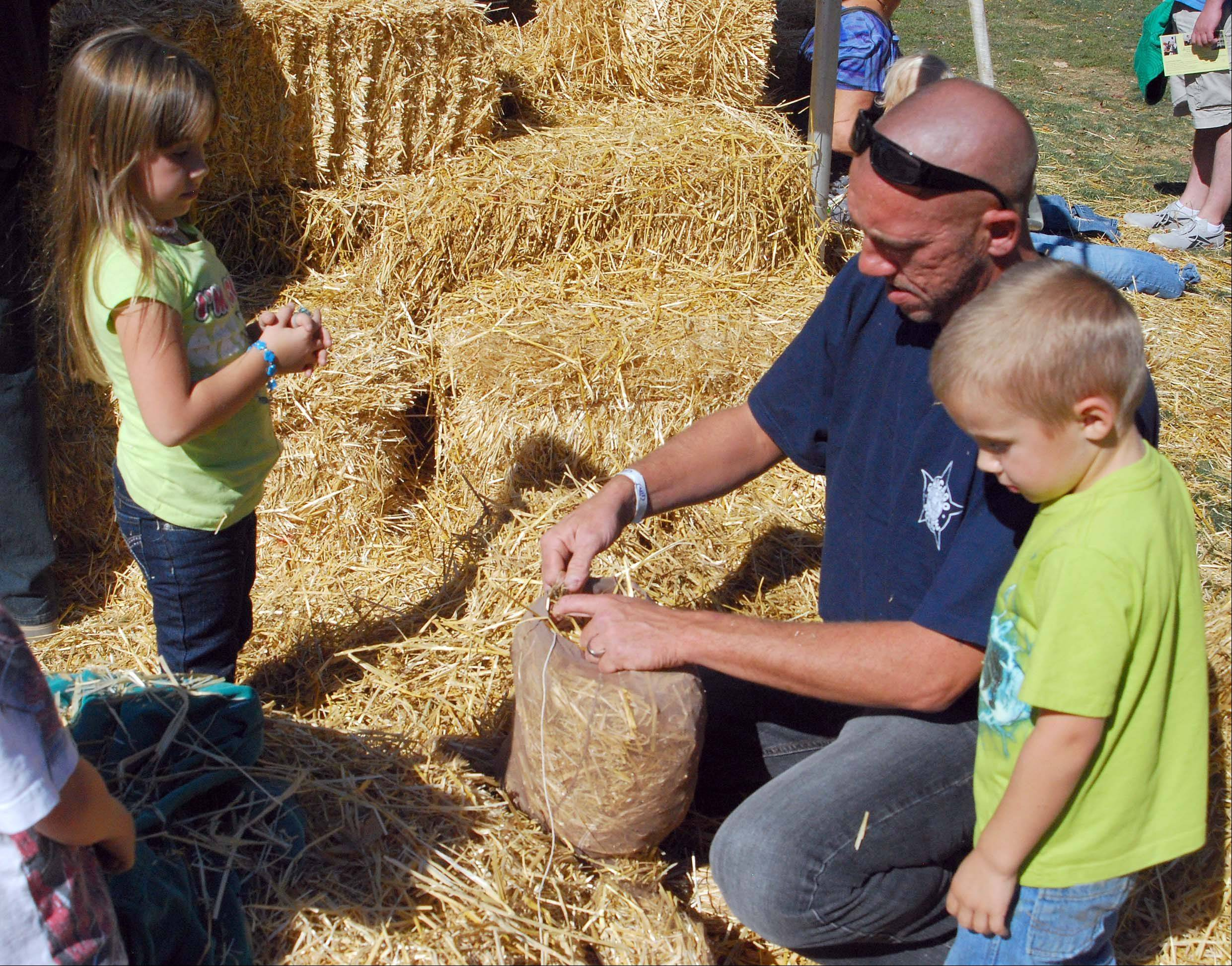 Michael Graiber helps his children Kendall, 5, and Devin, 4, stuff straw into stockings to build a scarecrow Sunday during the third and final day of Huntley Fall Fest at Deicke Park.