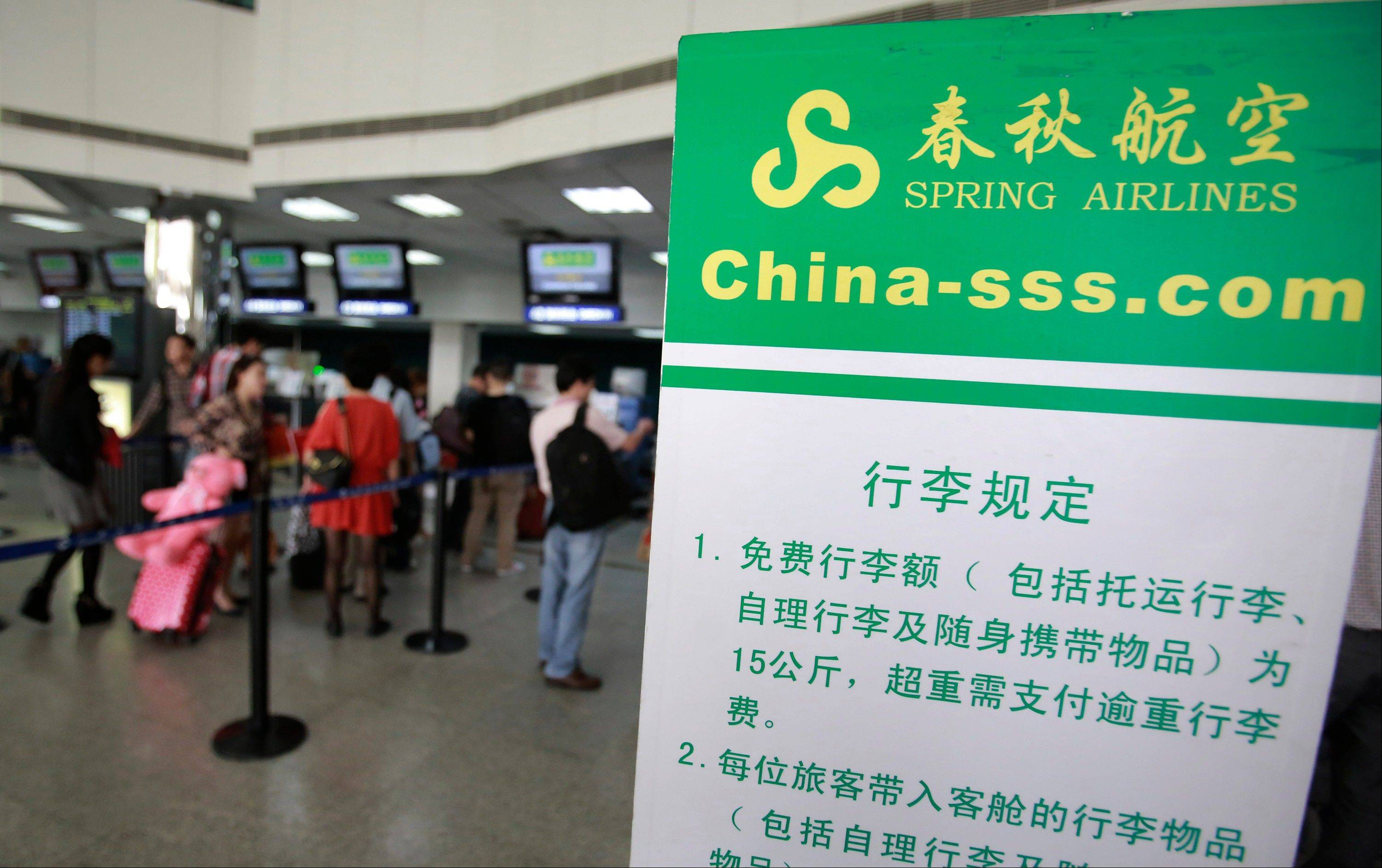 Passengers line up at a check-in counter of Spring Airline at Hongqiao Airport in Shanghai, China. A budget airline boom that is sweeping Asia is leaving Chinese travelers behind. From almost none a decade ago, the region now has more than 50 low cost carriers. But China's government still keeps tight control of the rapidly growing airline industry.