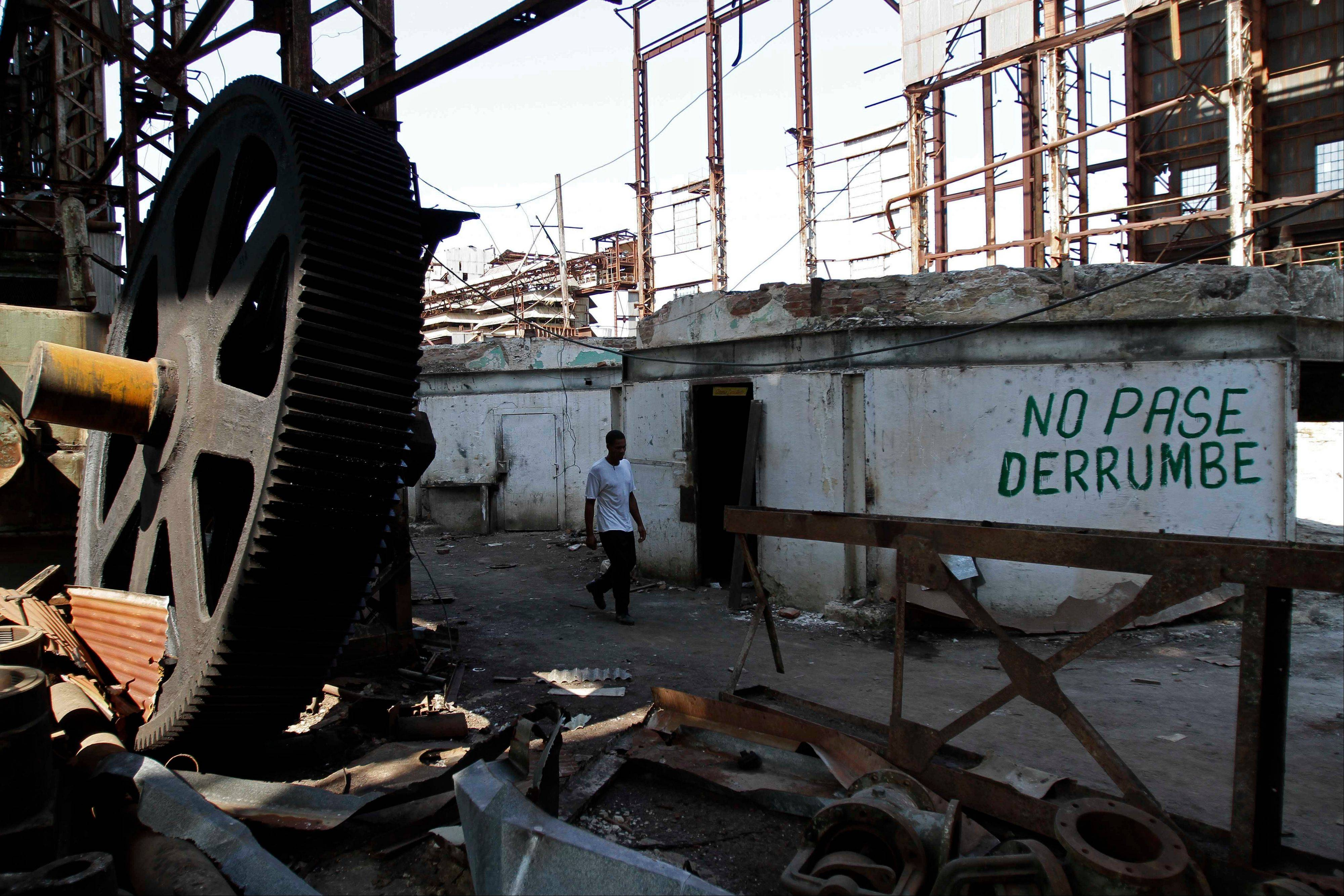"A worker walks among old machinery at the sugar processing plant ""Brasil"" in Jaronu, Cuba. The words written on the wall read in Spanish ""Don't pass. Collapse."" The Brasil sugar plant, launched in 1921, is getting a makeover and is expected to be ready in time for the upcoming annual harvest and start milling cane by February"