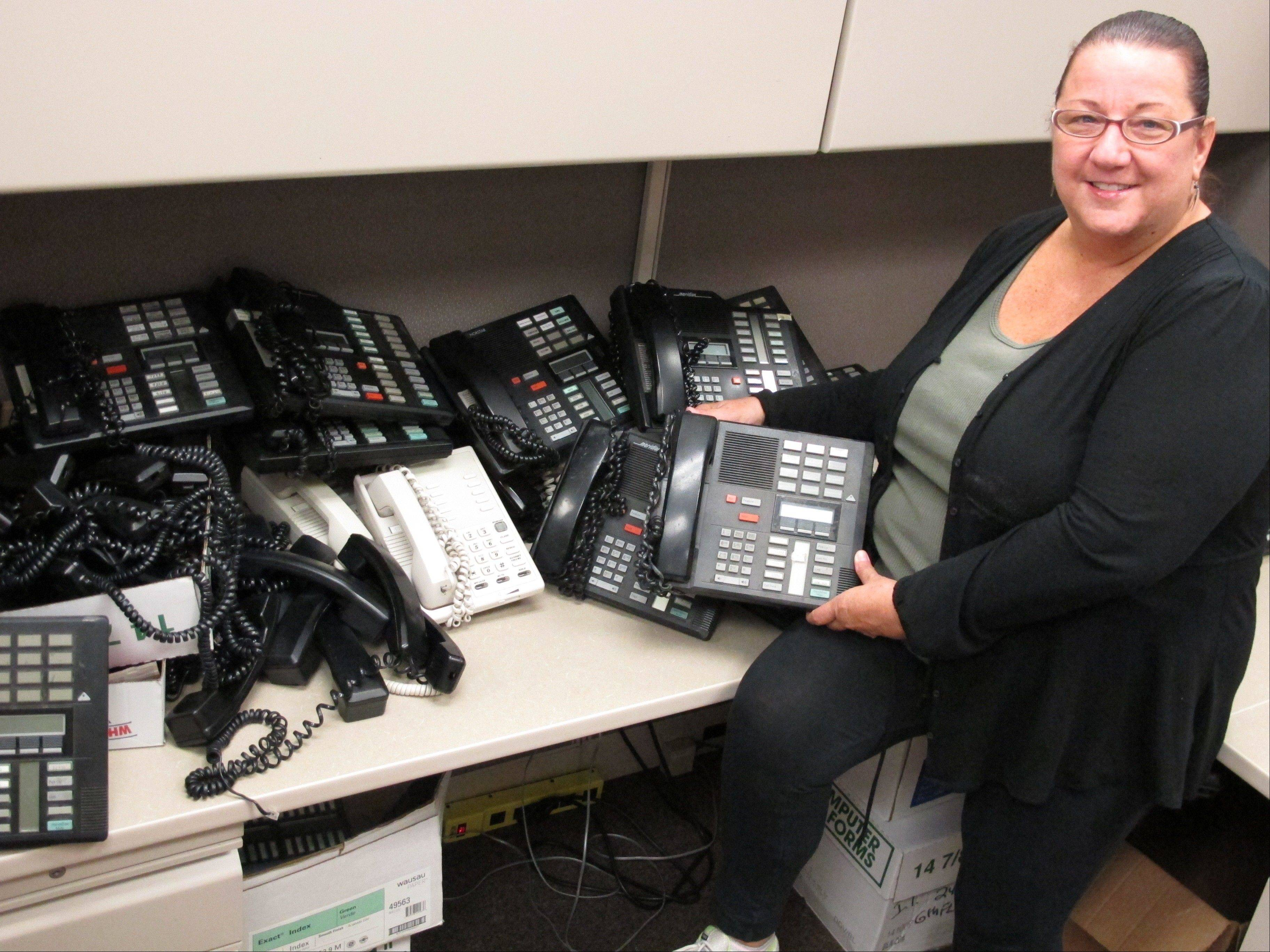 Mary Morgan, a Nassau County information technology specialist, poses with the telephones she is assessing as part of a countywide efficiency effort in Mineola, N.Y. Nassau County is currently shutting off hundreds of unused telephone lines and reviewing their current stock of telephones as part of a cost-cutting initiative.