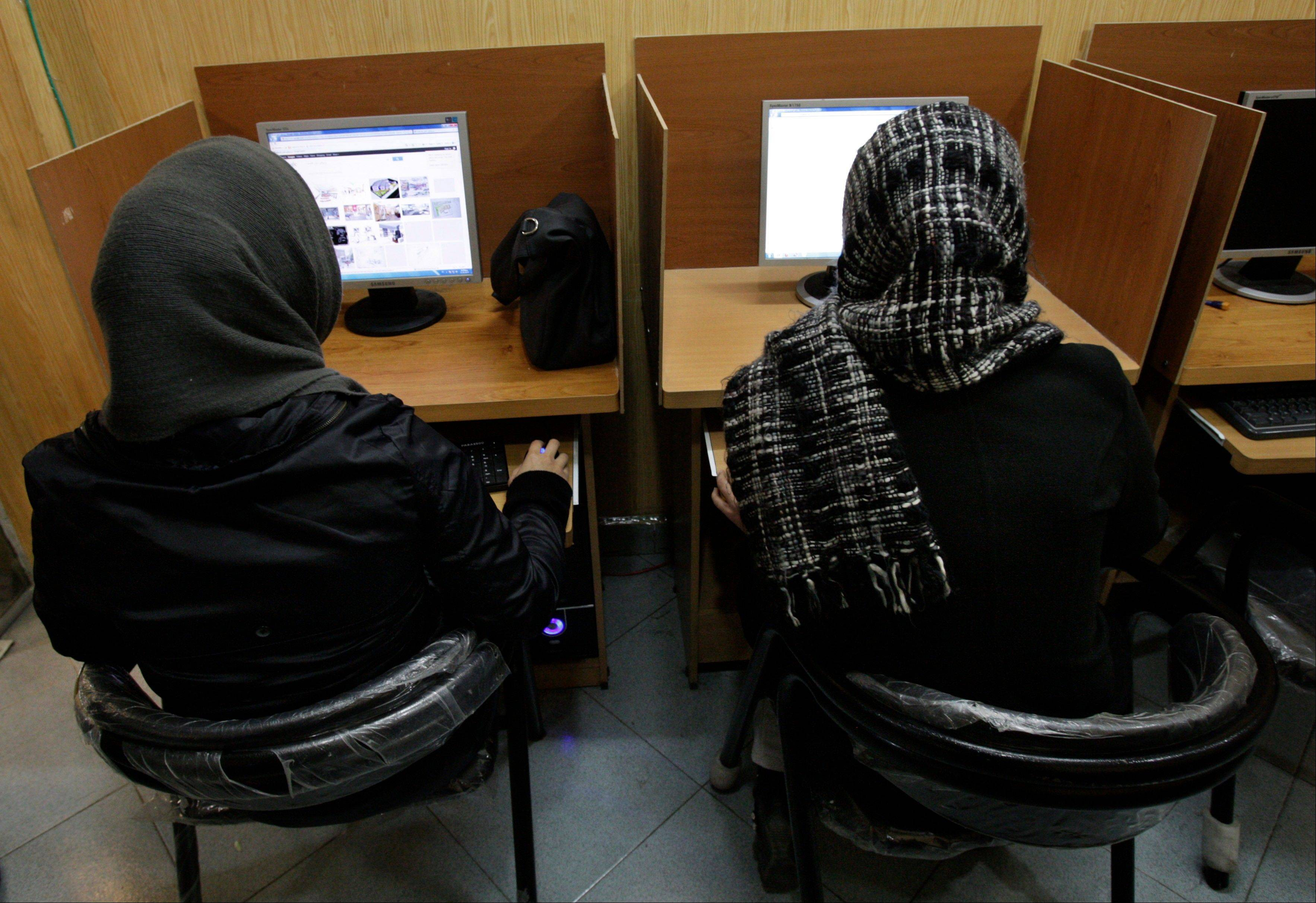 In this Feb. 13, 2012, file photo, Iranian women use computers at an Internet cafe in central Tehran. Iran's cyber monitors often tout their efforts to fight the Westís 'soft war' of influence through the Web, but trying to ban Google's popular Gmail may have gone too far with complaints coming even from email-starved parliament members.