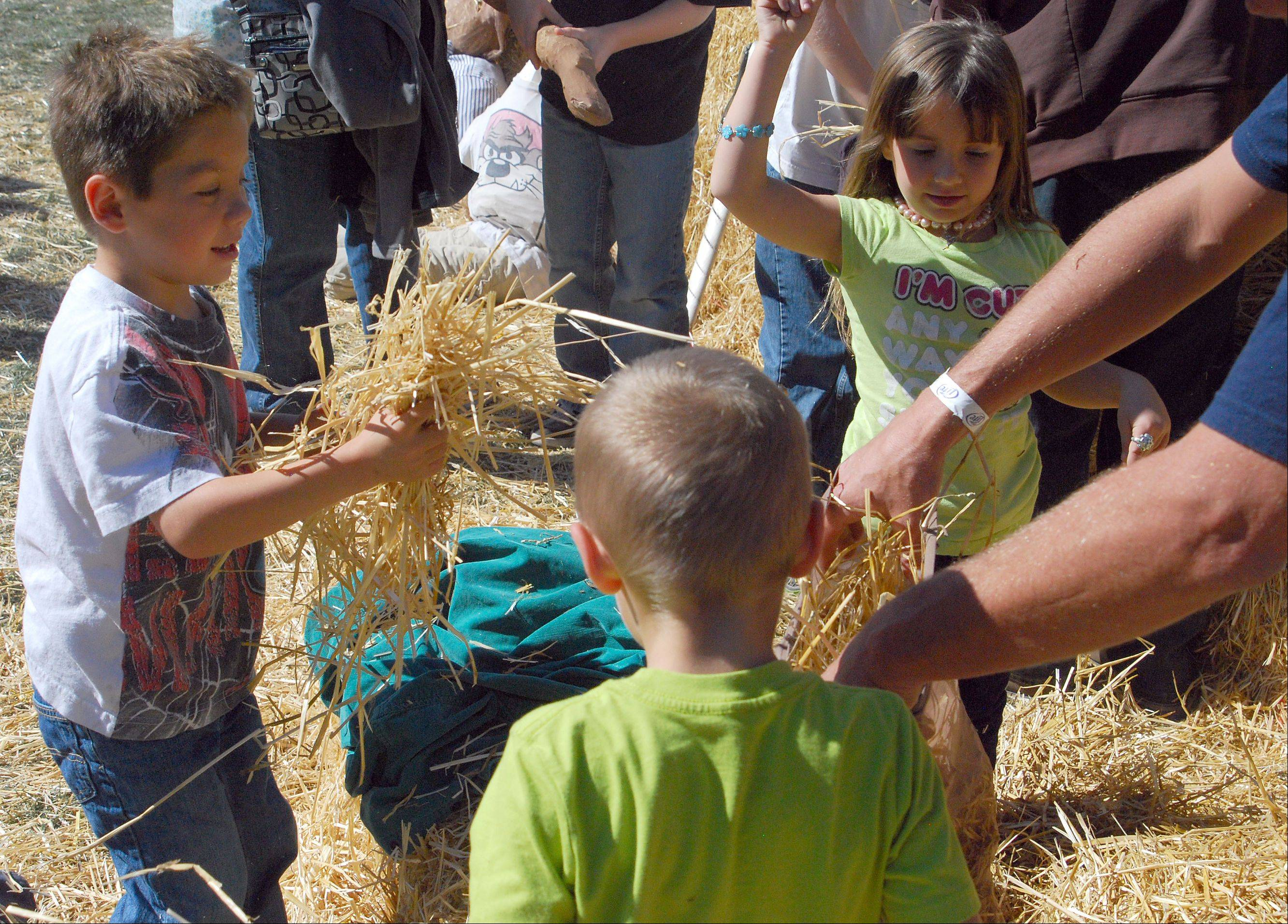 Payton Graiber, 5, stuffs straw into the body of a scarecrow he built with his father, Michael Graiber, and his siblings, Kendall, 5, and Devin, 4, Sunday at Huntley Fall Fest at Deicke Park.