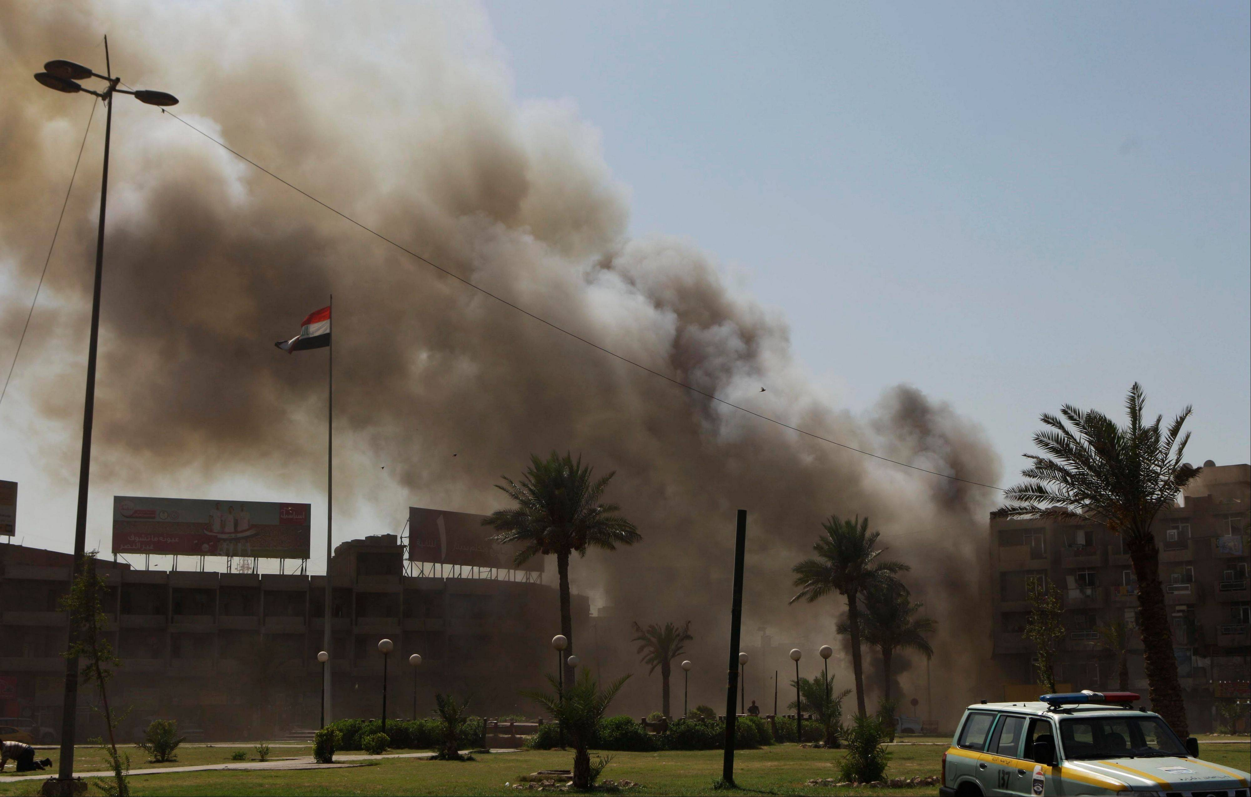 Plumes of smoke rise from the scene of a car bomb attack Sunday near the Sacred Heart Church in the Karrada Neighborhood of Baghdad, Iraq. A rapid-fire series of explosions in Baghdad while Iraqis were going to work on Sunday morning, killed and wounded scores of people, police said.