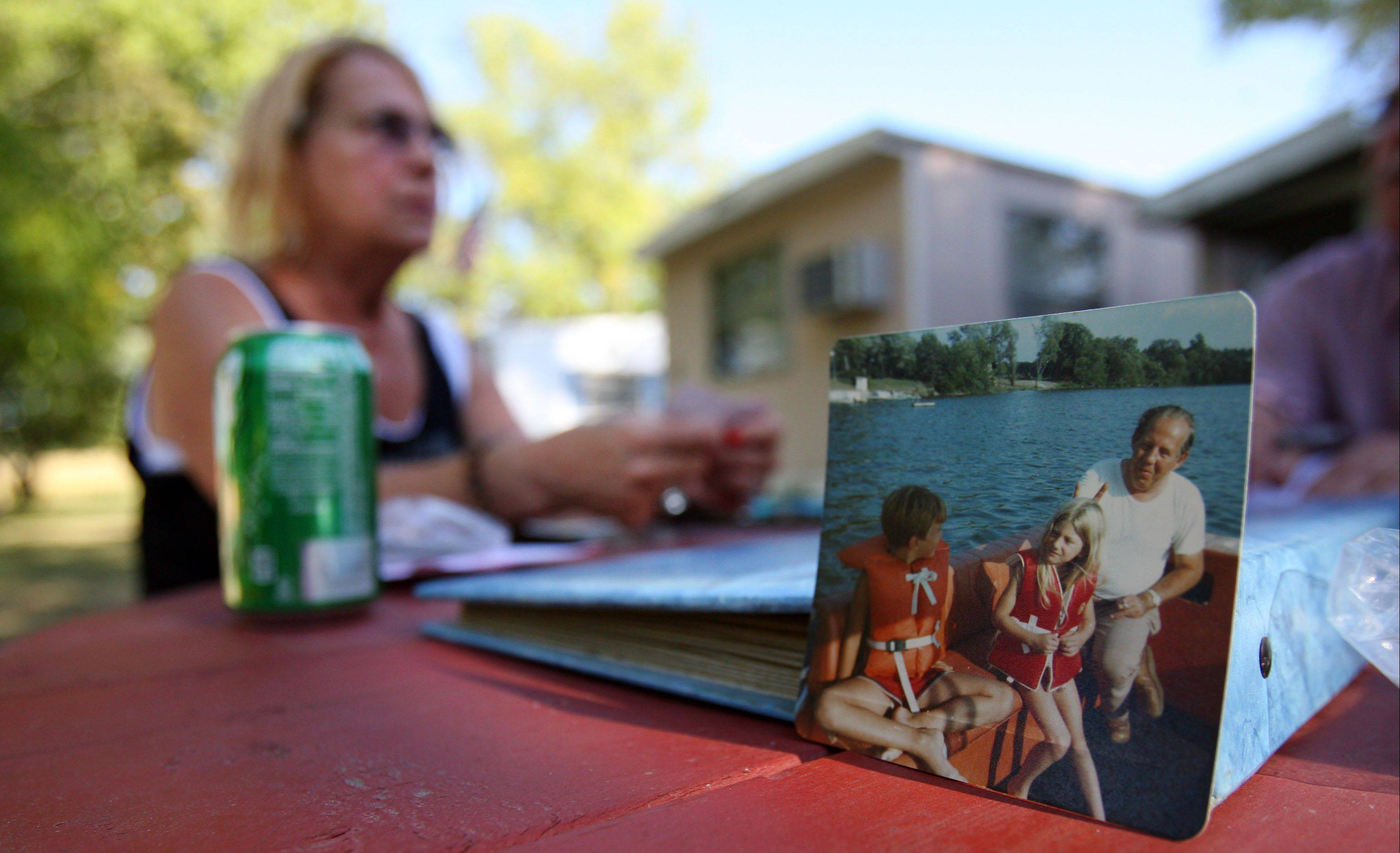 Carol Rychlee of Wilmette reminisces as she looks through old pictures of her life at Lake Marie Camp near Antioch.