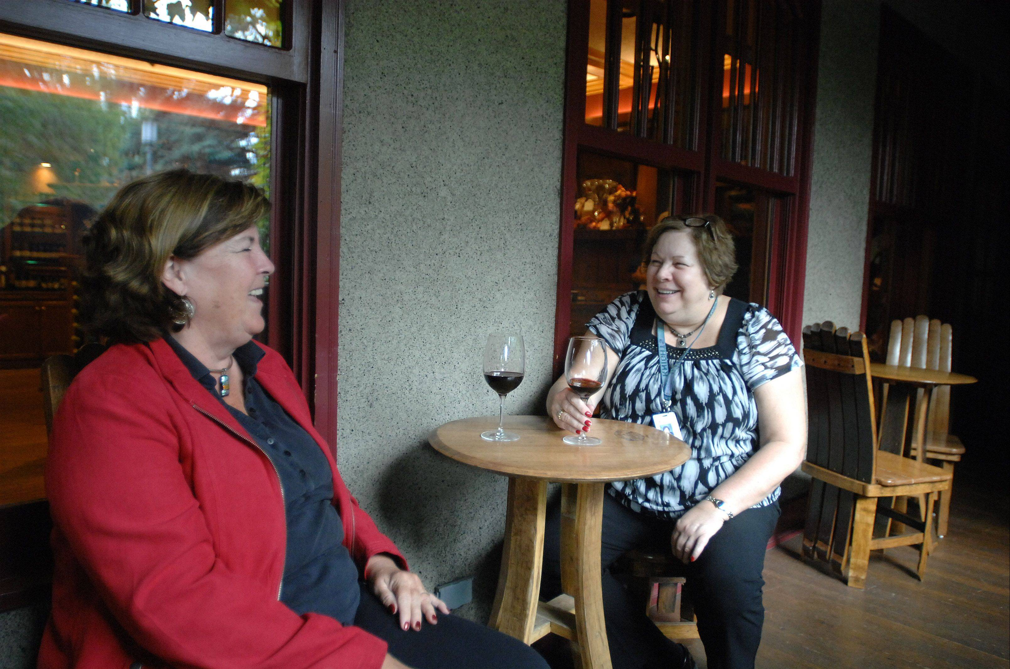 Maggie Roland of Wheeling, left, and Jo Holtby of Arlington Heights have a glass of wine at the Lynfred Winery in Roselle after attending the Ryder Cup. The winery has seen a substantial boost in business from the event.