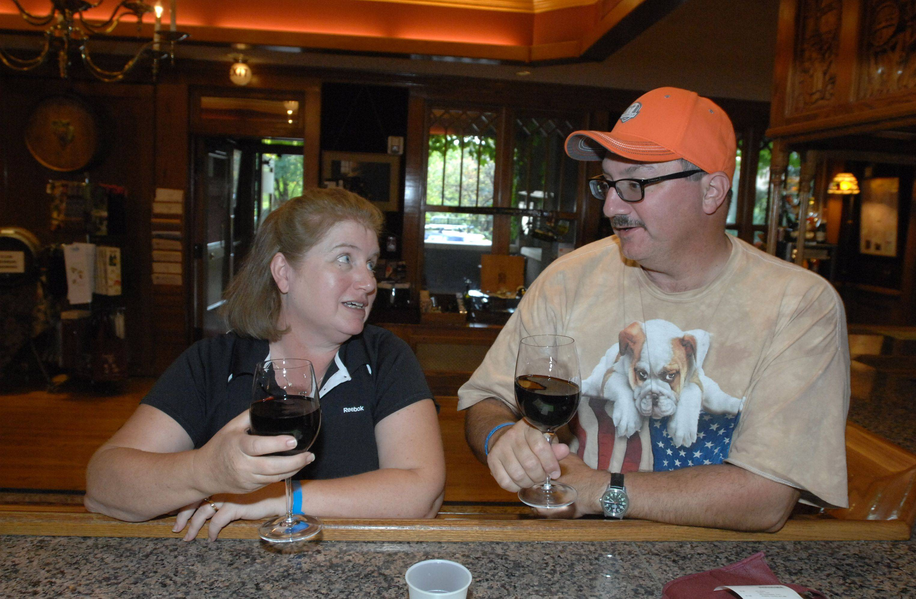 Kristy Glass, left, and Jeff Glass of Schaumburg have a glass of wine at the Lynfred Winery in Roselle after attending the Ryder Cup. The winery has seen a substantial boost in business from the event.