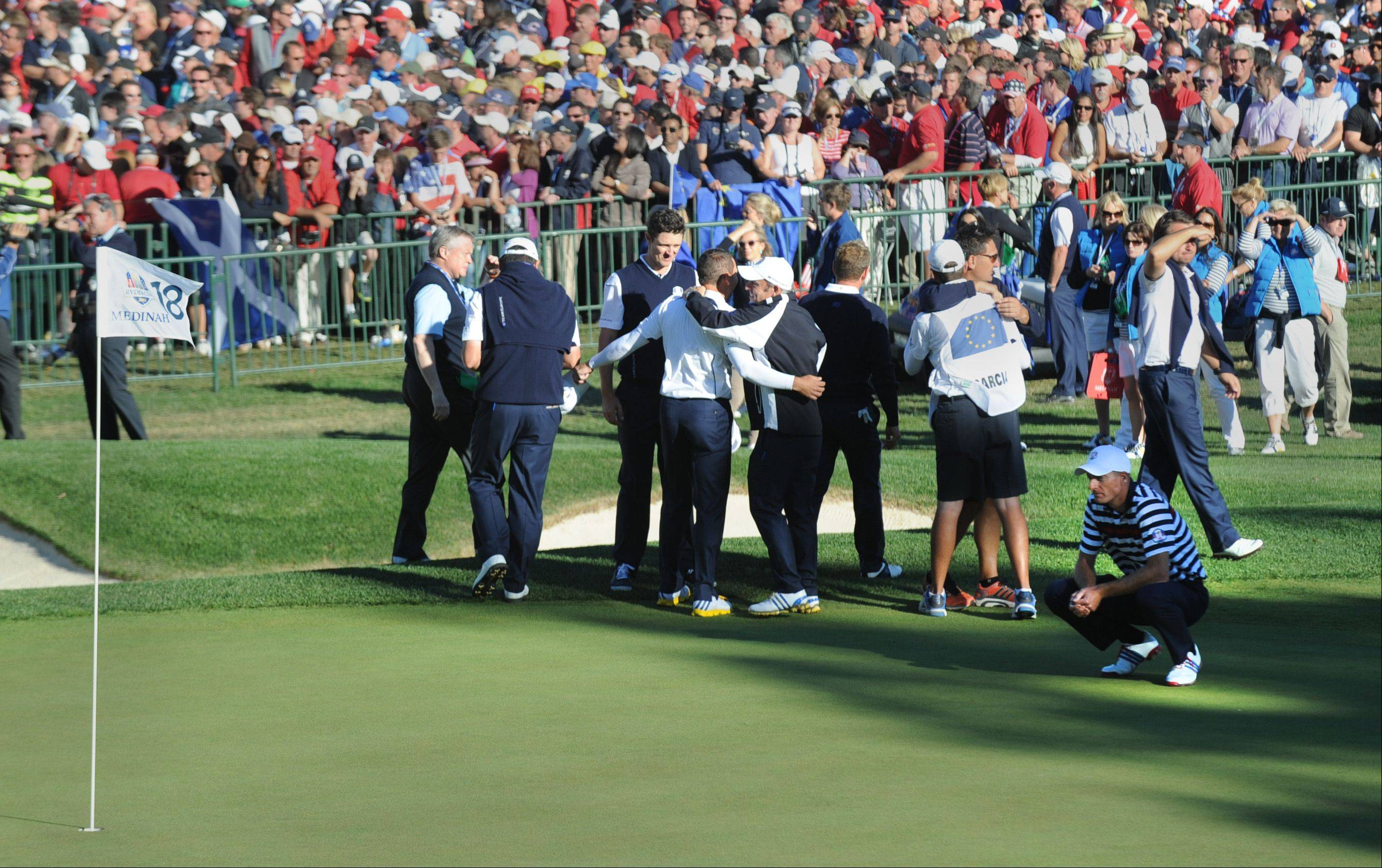 Jim Furyk remains dejected on the 18th green after missing a putt and losing his Ryder Cup singles match to Sergio Garcia as European players and coaches celebrate Sunday.