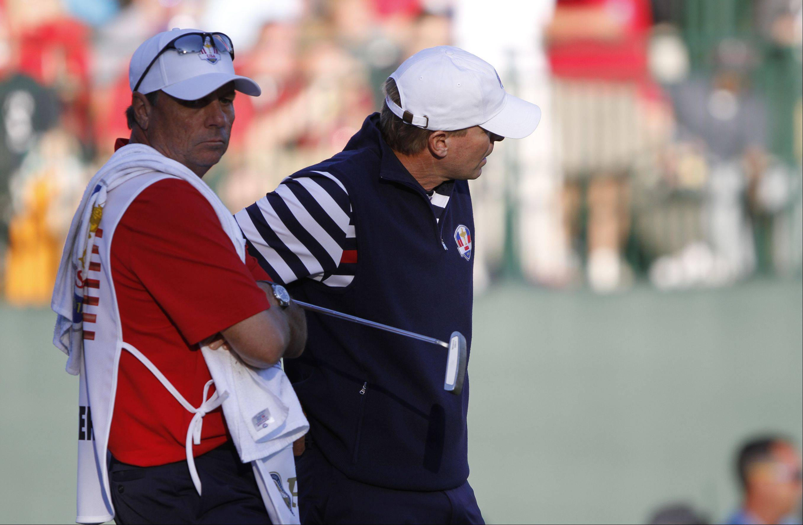 Steve Stricker and his caddy look glum after Stricker missed a putt on the 18th that sealed the European victory Sunday at the 2012 Ryder Cup at Medinah Country Club.