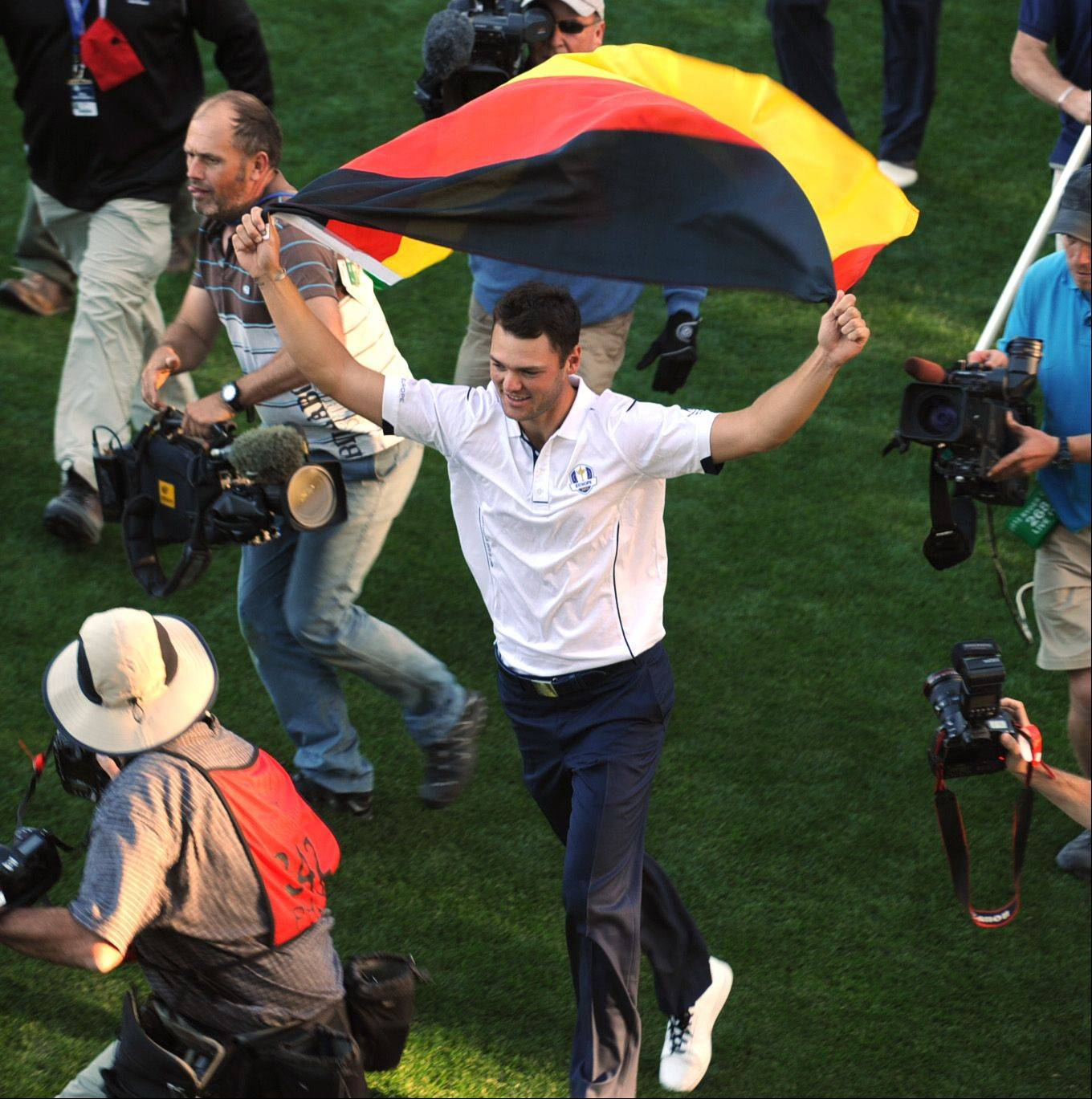 Martin Kaymer of Germany celebrates with his country's flag after his putt won the cup for the European team.