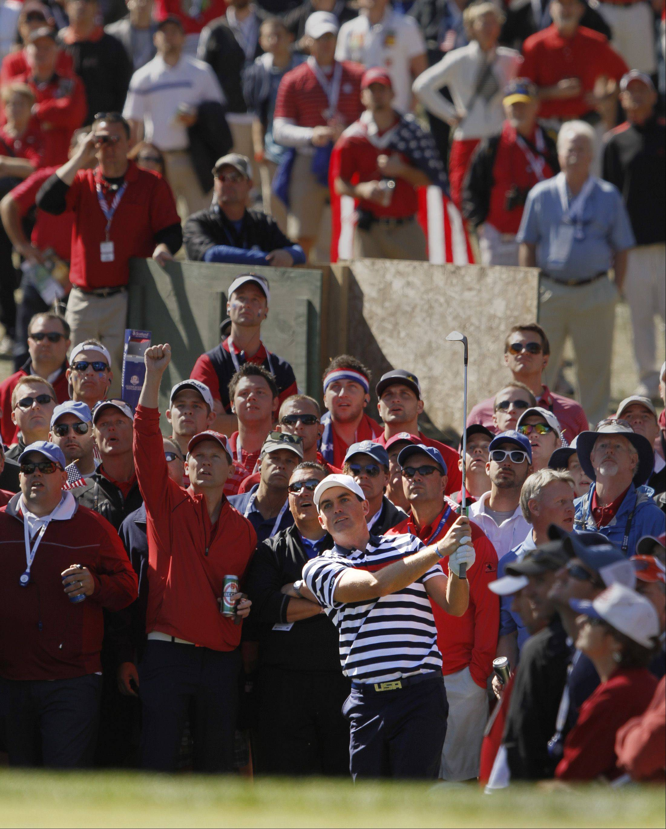 Keegan Bradley fires a shot from the rough as the crowd watches in anticipation.