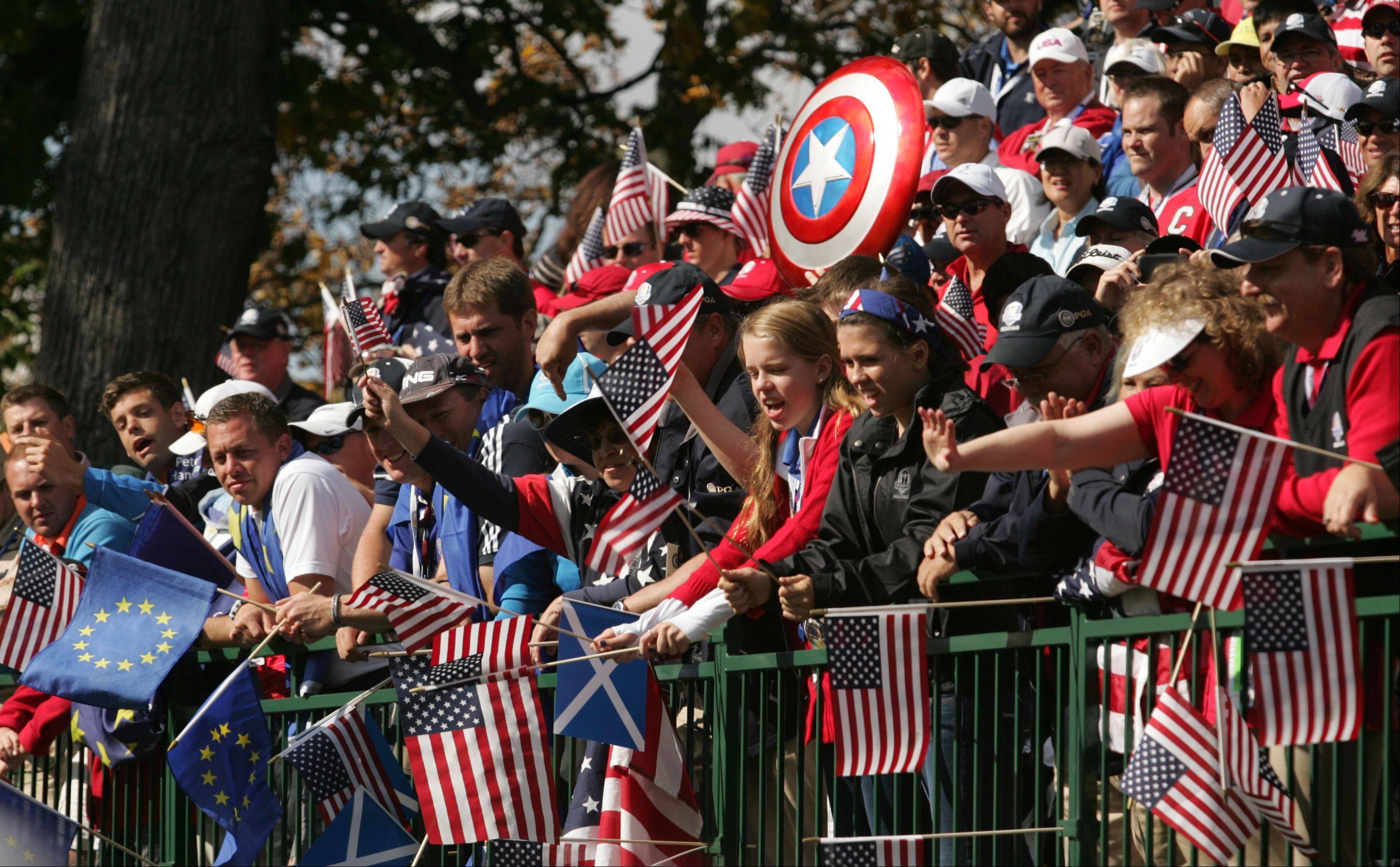 Fans clamor for freebies being tossed out by the Team USA assistant captain as they wait for the start of the final day of the Ryder Cup at Medinah.