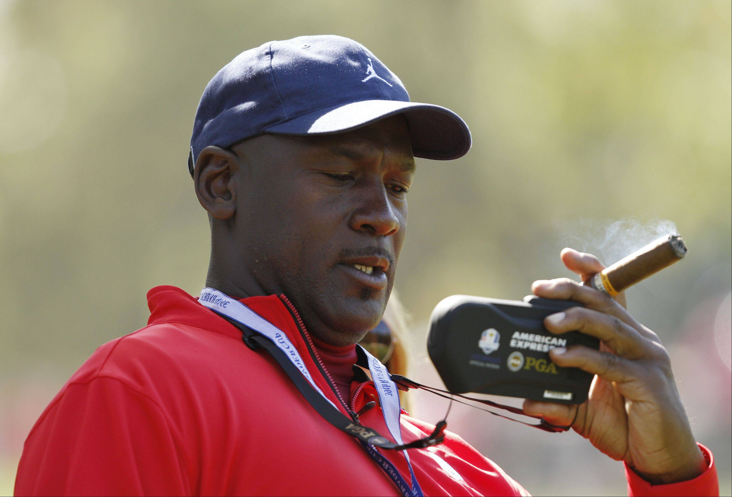 Michael Jordan watches some live action on a remote device while enjoying a cigar on the course Sunday.
