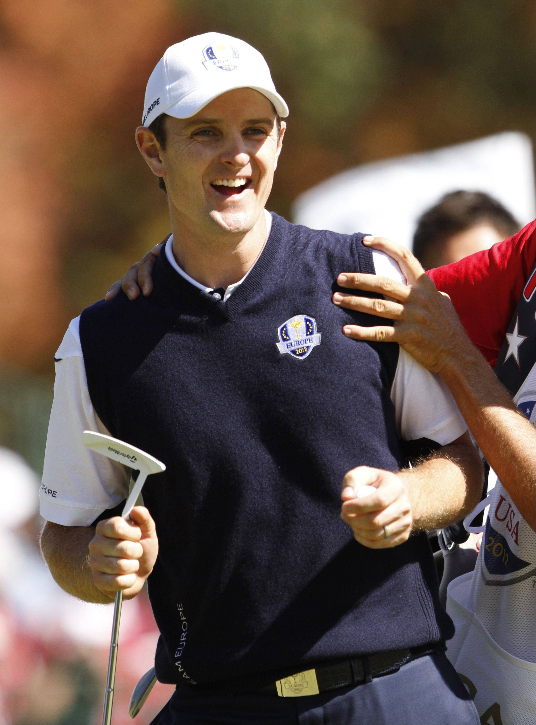 Team Europe's Justin Rose gets a hug from his caddie Sunday during the singles matches.