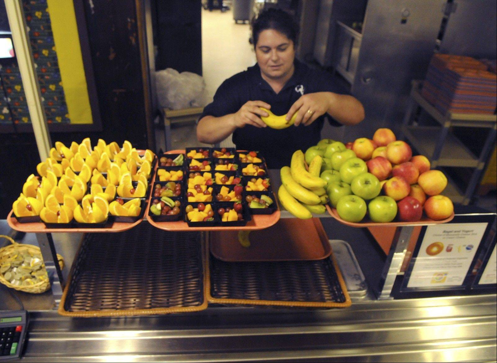 Samantha Hiller arranges the fresh fruit at Quaker Valley�s Anthony Wayne Middle School. New federal school lunch regulations are changing how cafeteria workers prepare and present food, such as creating eye-catching display to entice students.