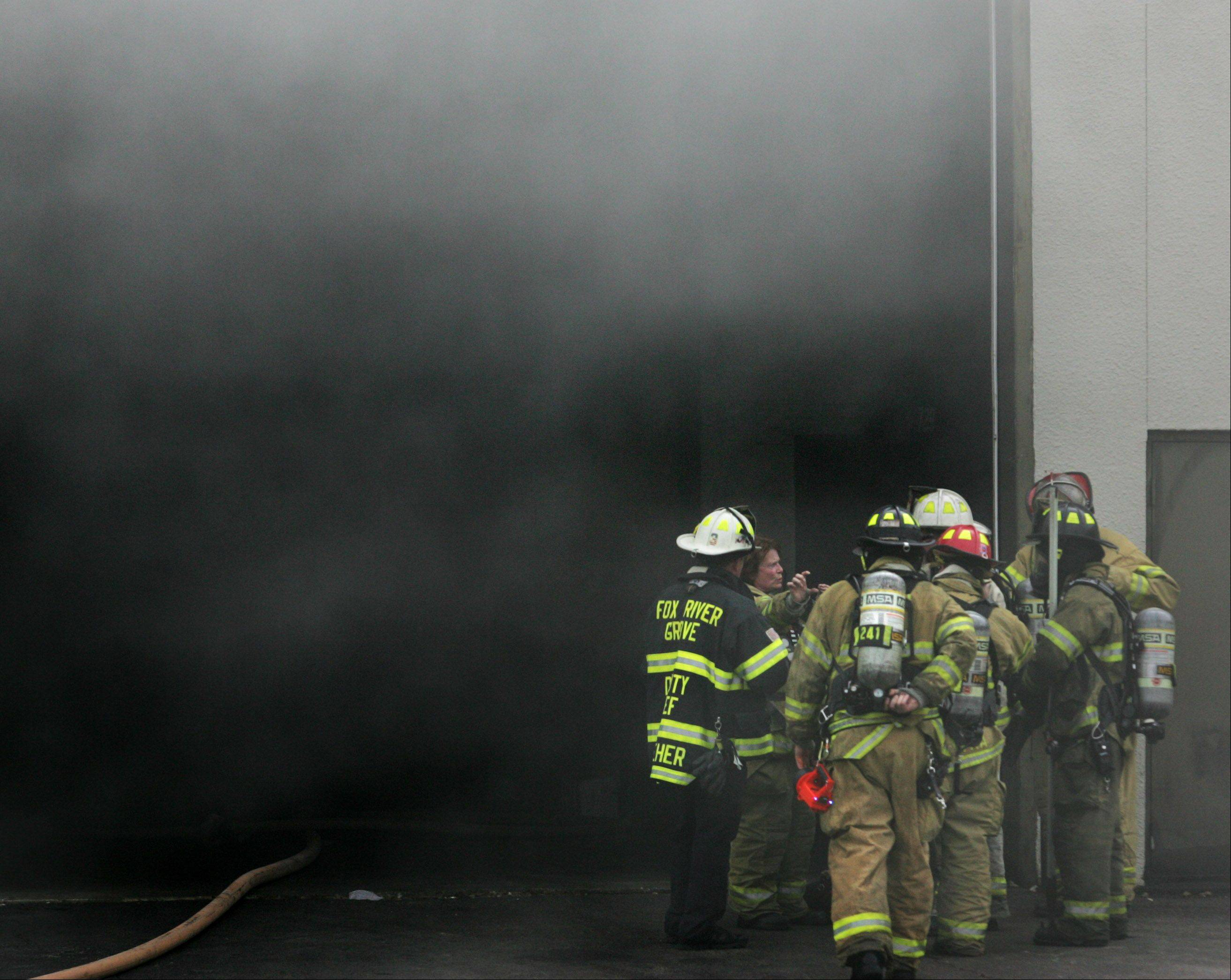 Firefighters from Cary and Fox River Grove Fire Protection District coordinate their efforts while at the scene of a fire at the Tru-Cut factory in Cary Monday afternoon.